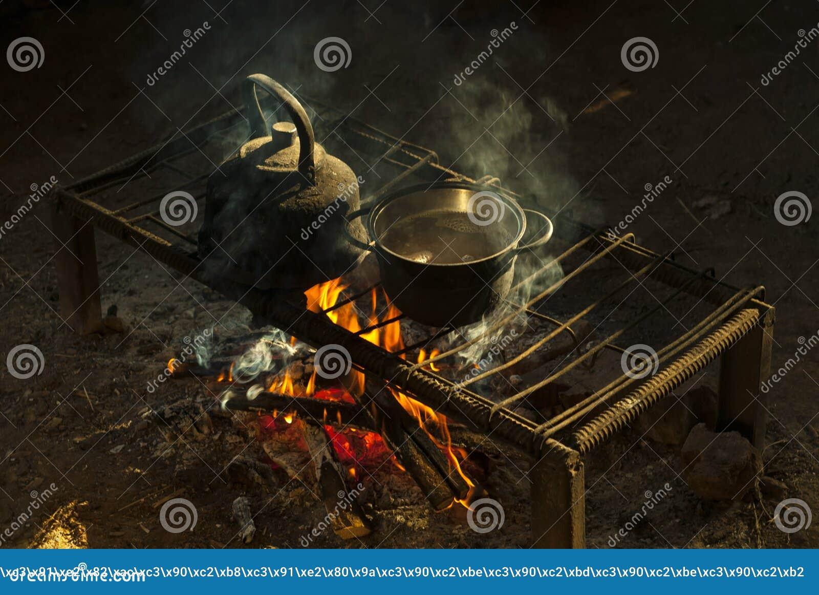 Um potenciômetro e uma chaleira em uma lareira portátil feita das hastes de metal em uma moradia do ` s do nômada