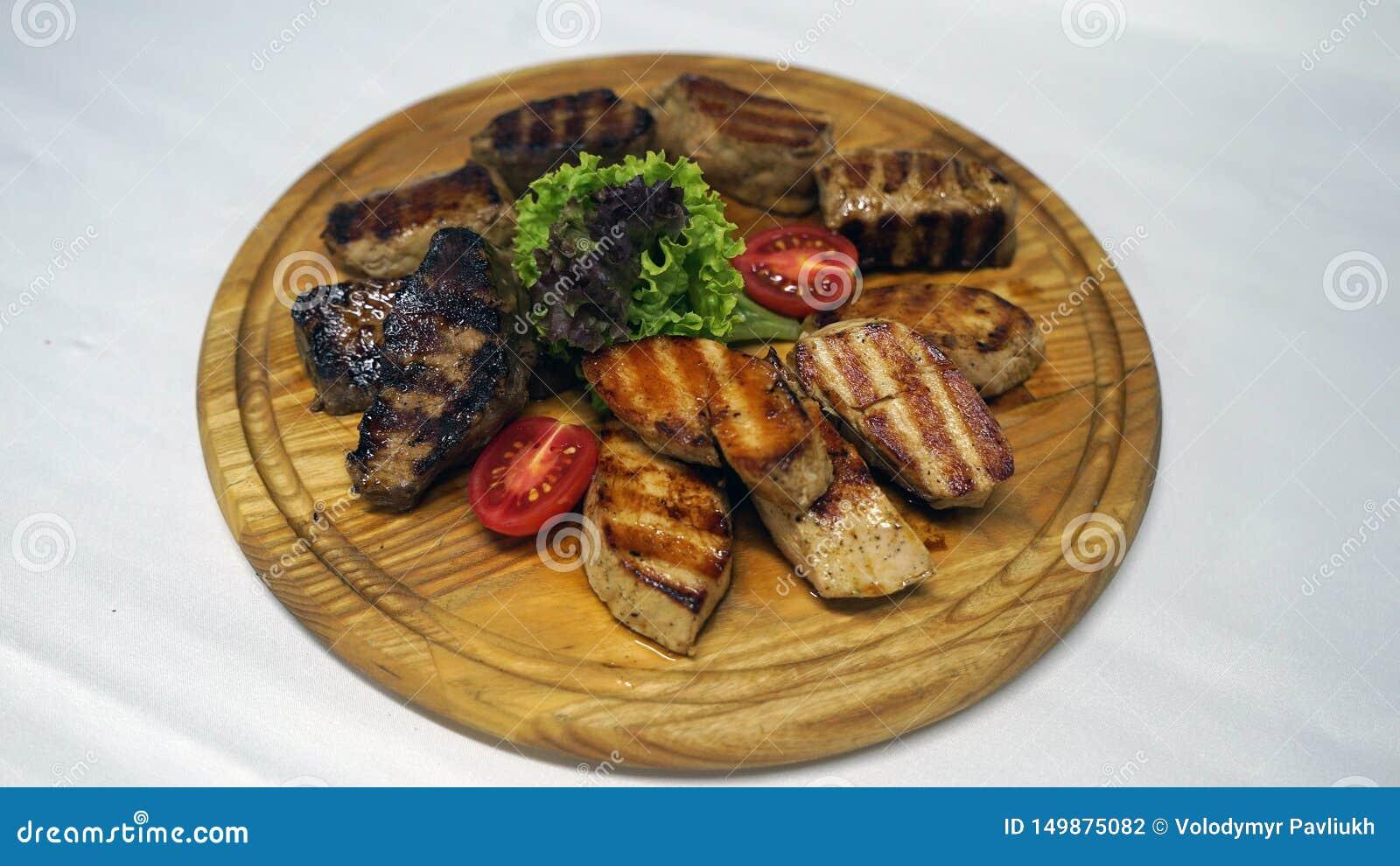 Um prato maravilhoso da carne cozinhado em um assado com os reforços suculentos e as folhas da alface e apresentado na madeira