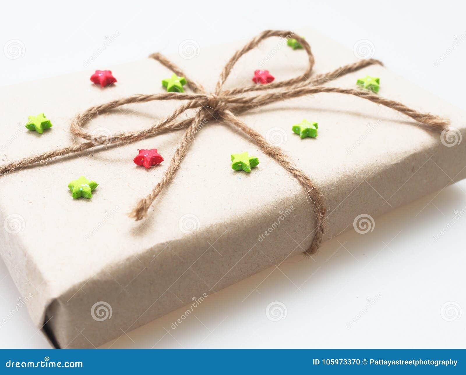 Um presente ou uma caixa de presente envolvido pelo marrom áspero reciclaram o papel e amarrams com corda marrom do cânhamo como