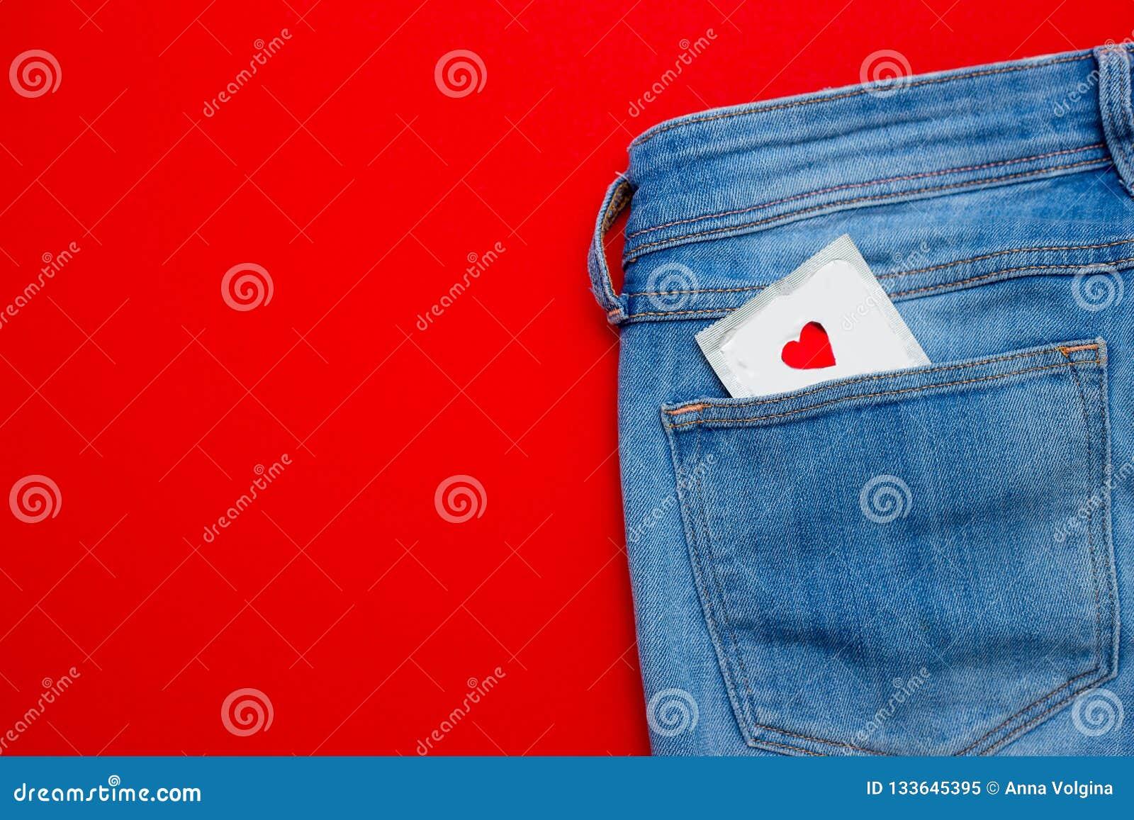 Um preservativo em um bolso das calças de brim Sexo seguro