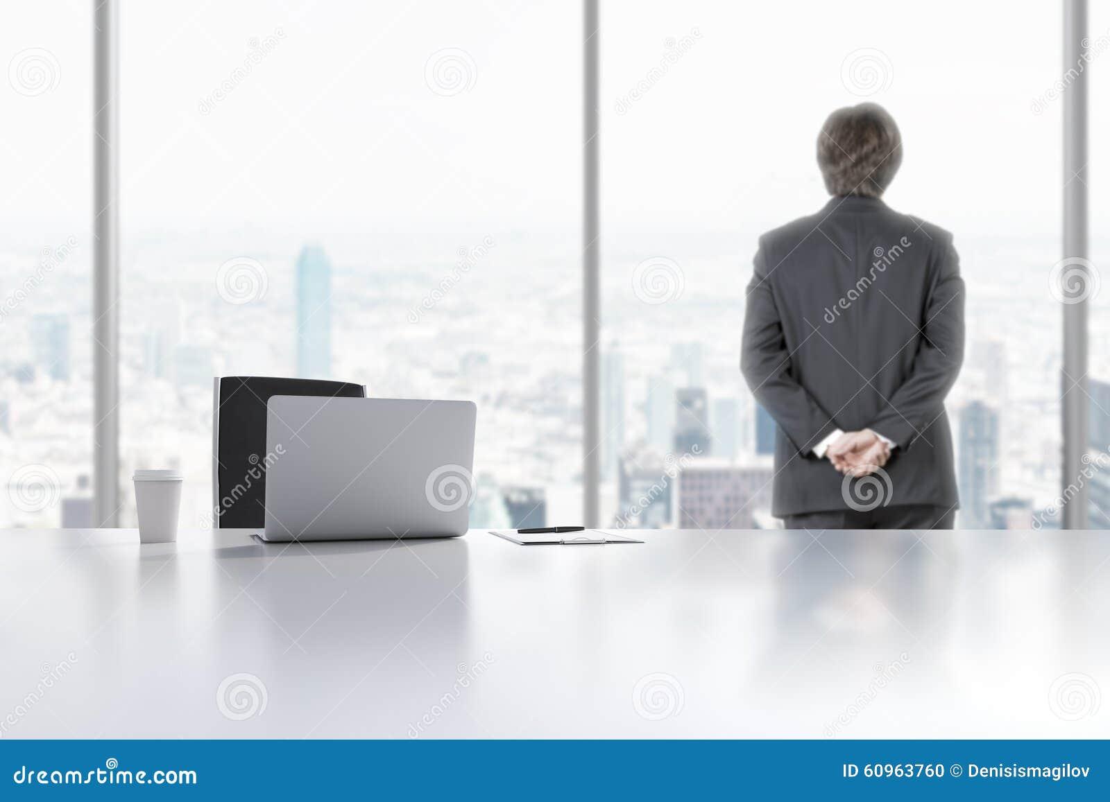 c410da628 Um profissional novo está olhando para fora a janela no escritório  panorâmico moderno em Manhattan, New York City Um portátil, o bloco de  notas e um copo de ...