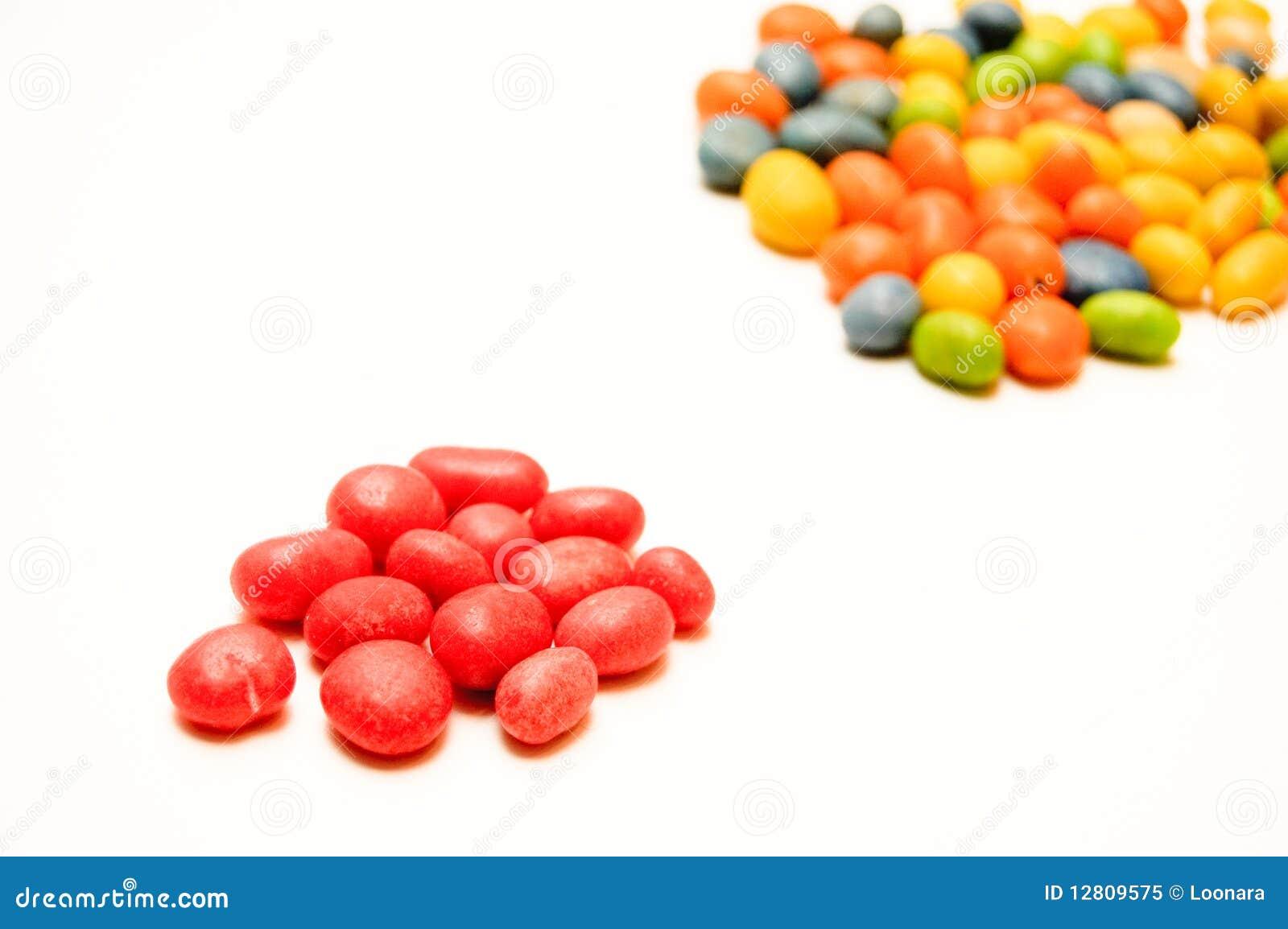 Um punhado de doces vermelhos no primeiro plano