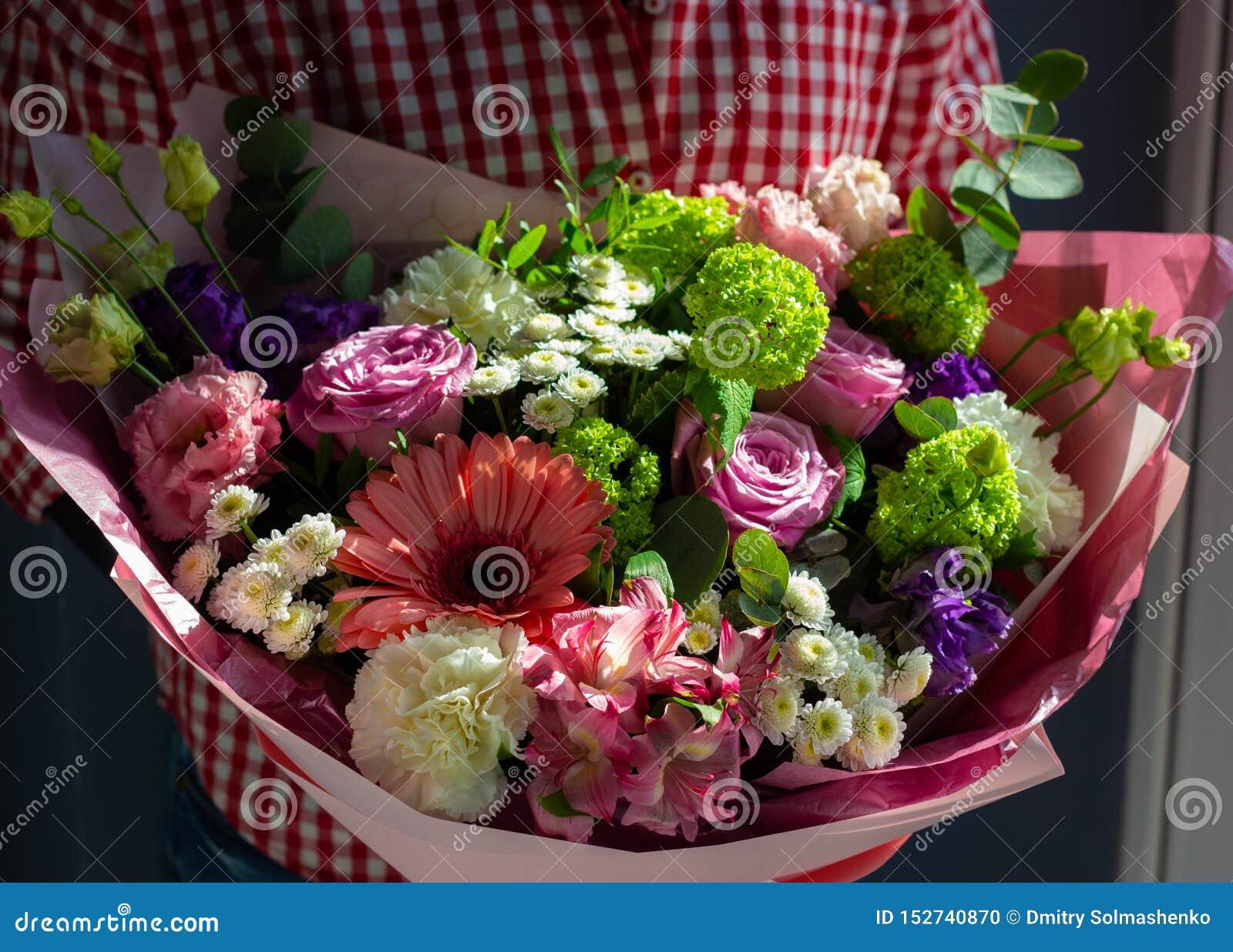 Um ramalhete brilhante de flores frescas nas mãos de uma moça