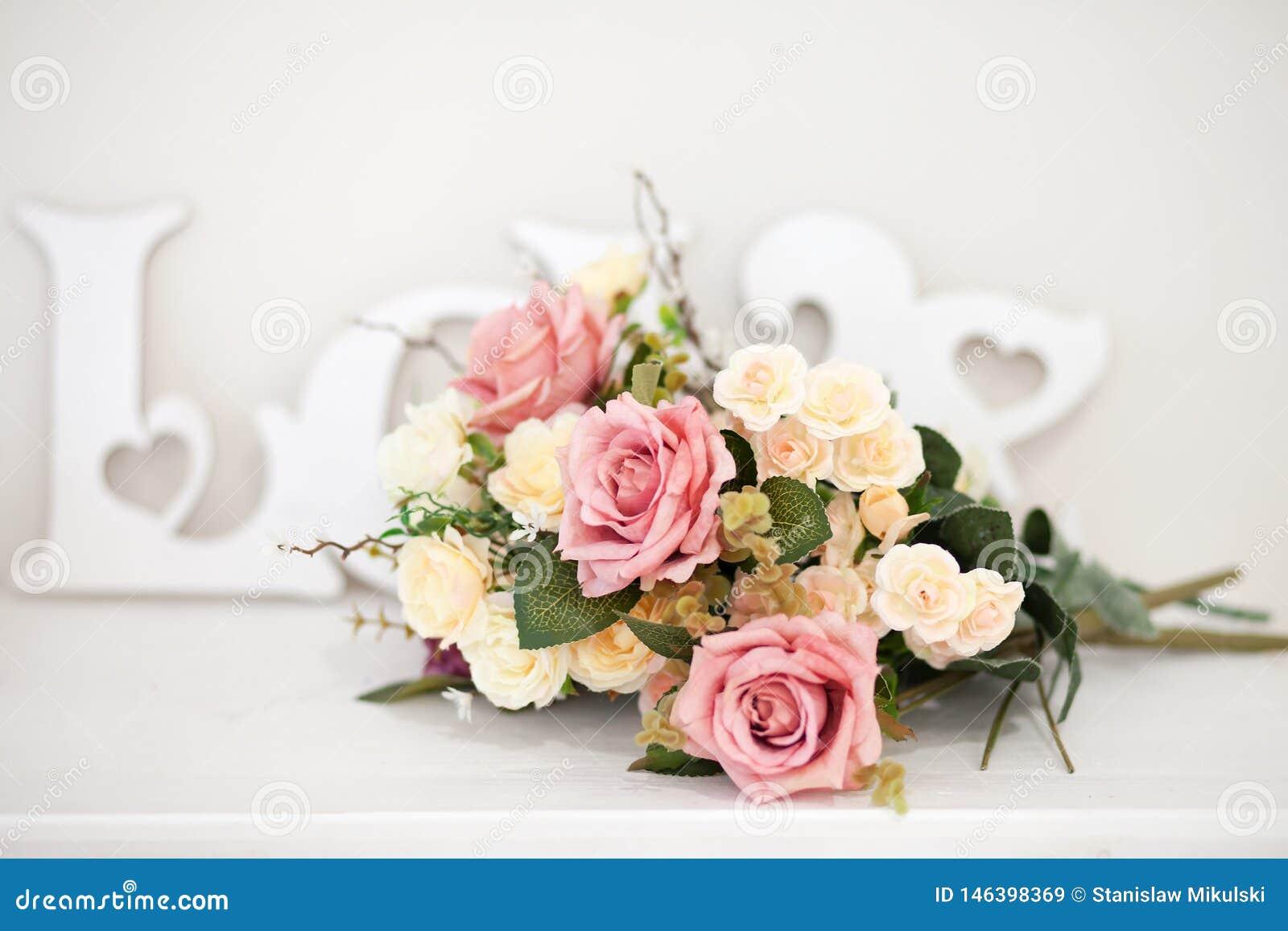 Um ramalhete de flores delicadas com um AMOR da inscrição