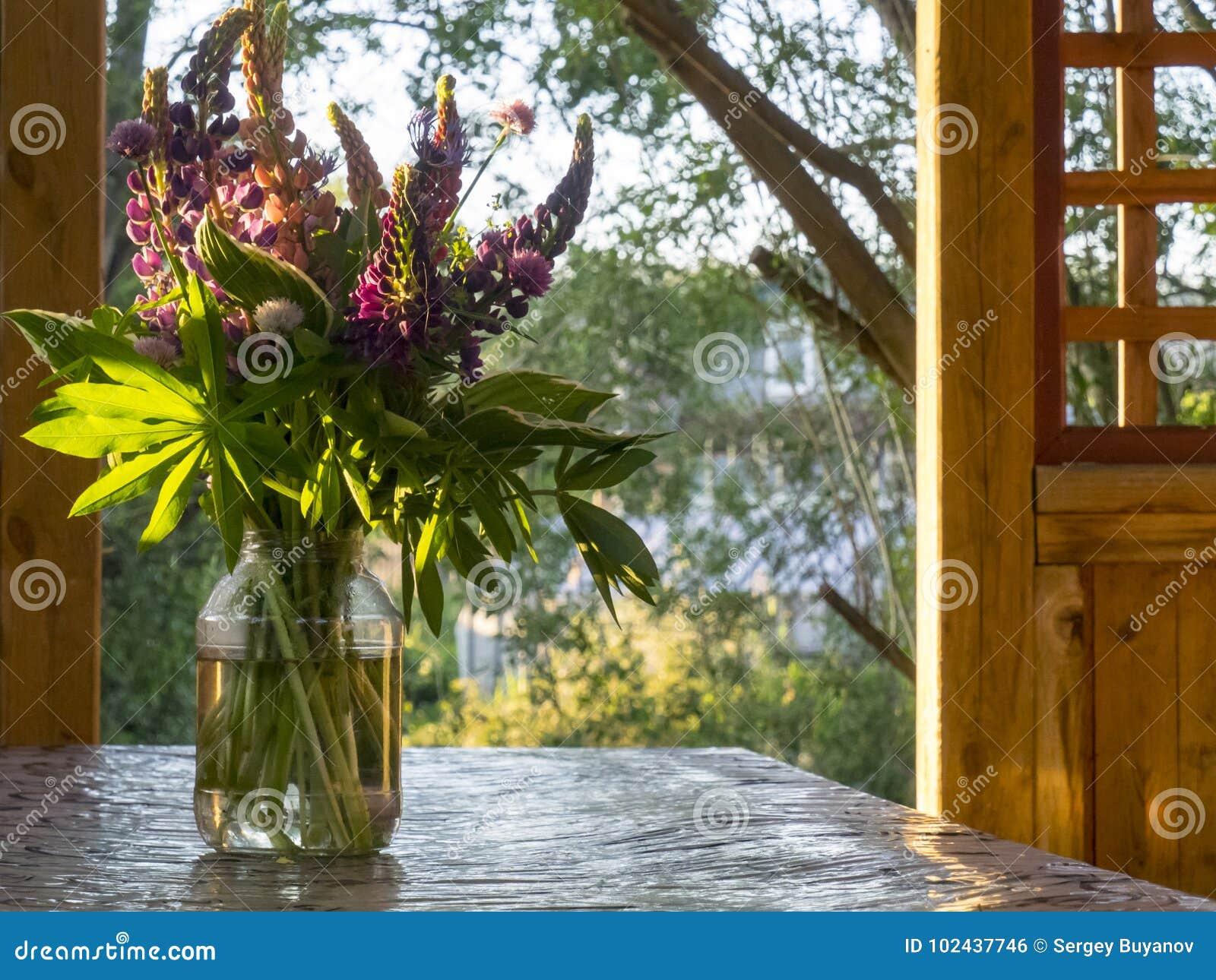 Um ramalhete dos lupines em um frasco na tabela, no patamar