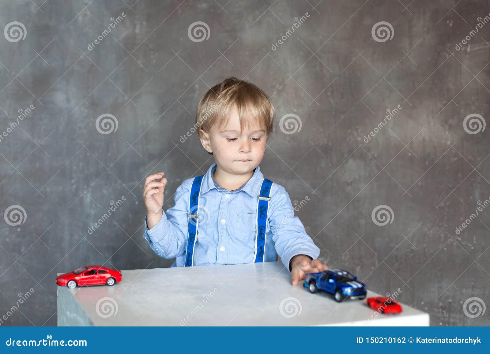 Um rapaz pequeno em uma camisa com suspensórios joga com carros coloridos do brinquedo do brinquedo os multi Menino pré-escolar q