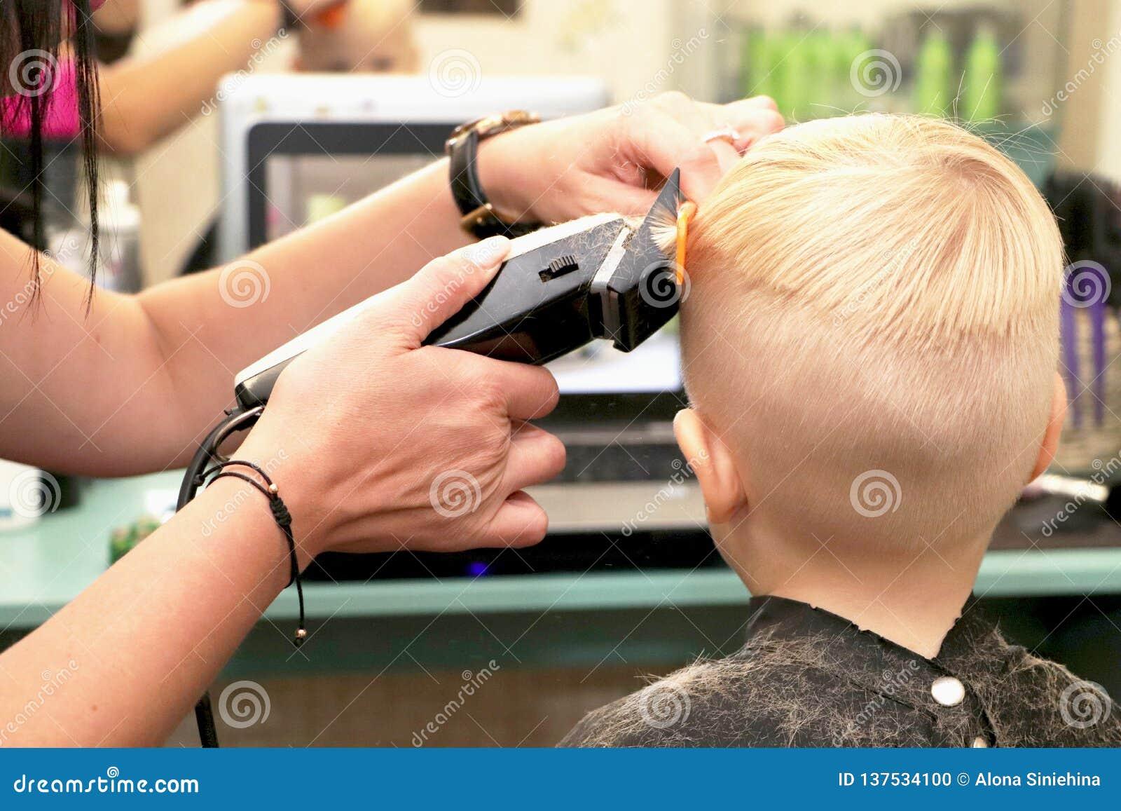 Um rapaz pequeno está cortando um cabeleireiro no salão de beleza A criança está olhando uns desenhos animados Tela verde em um p