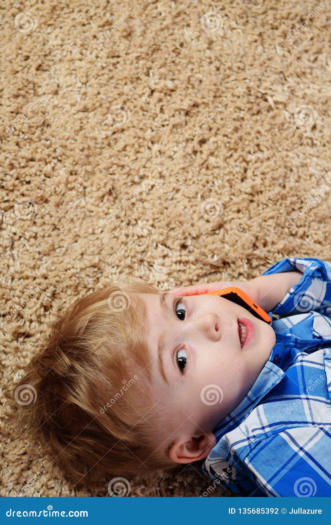 Um rapaz pequeno está encontrando-se no tapete e está jogando-se no telefone Rapaz pequeno que usa o smartphone