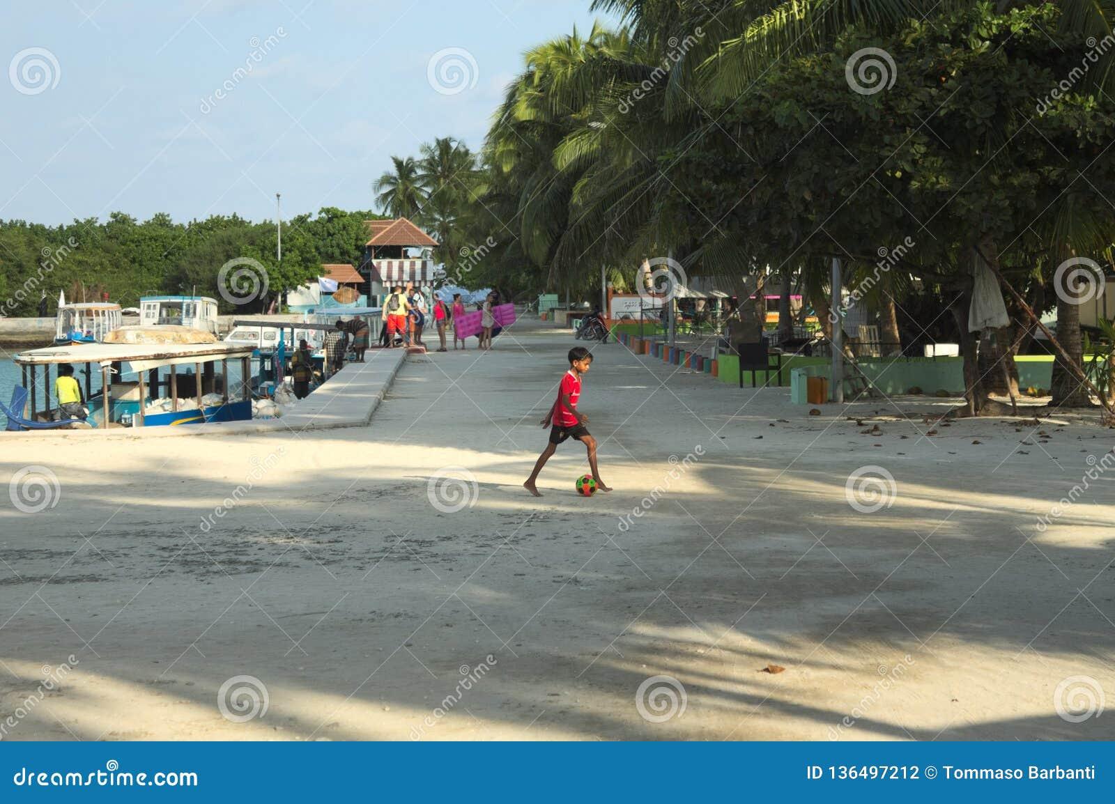 Um rapaz pequeno está jogando o futebol no porto