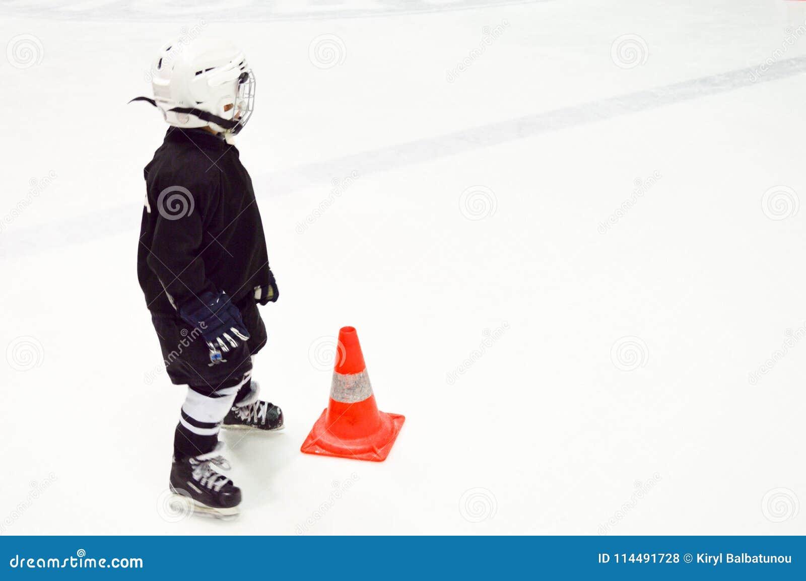 Um rapaz pequeno no uniforme preto do hóquei e um capacete branco em patins ao lado de um cone alaranjado no gelo branco no hóque