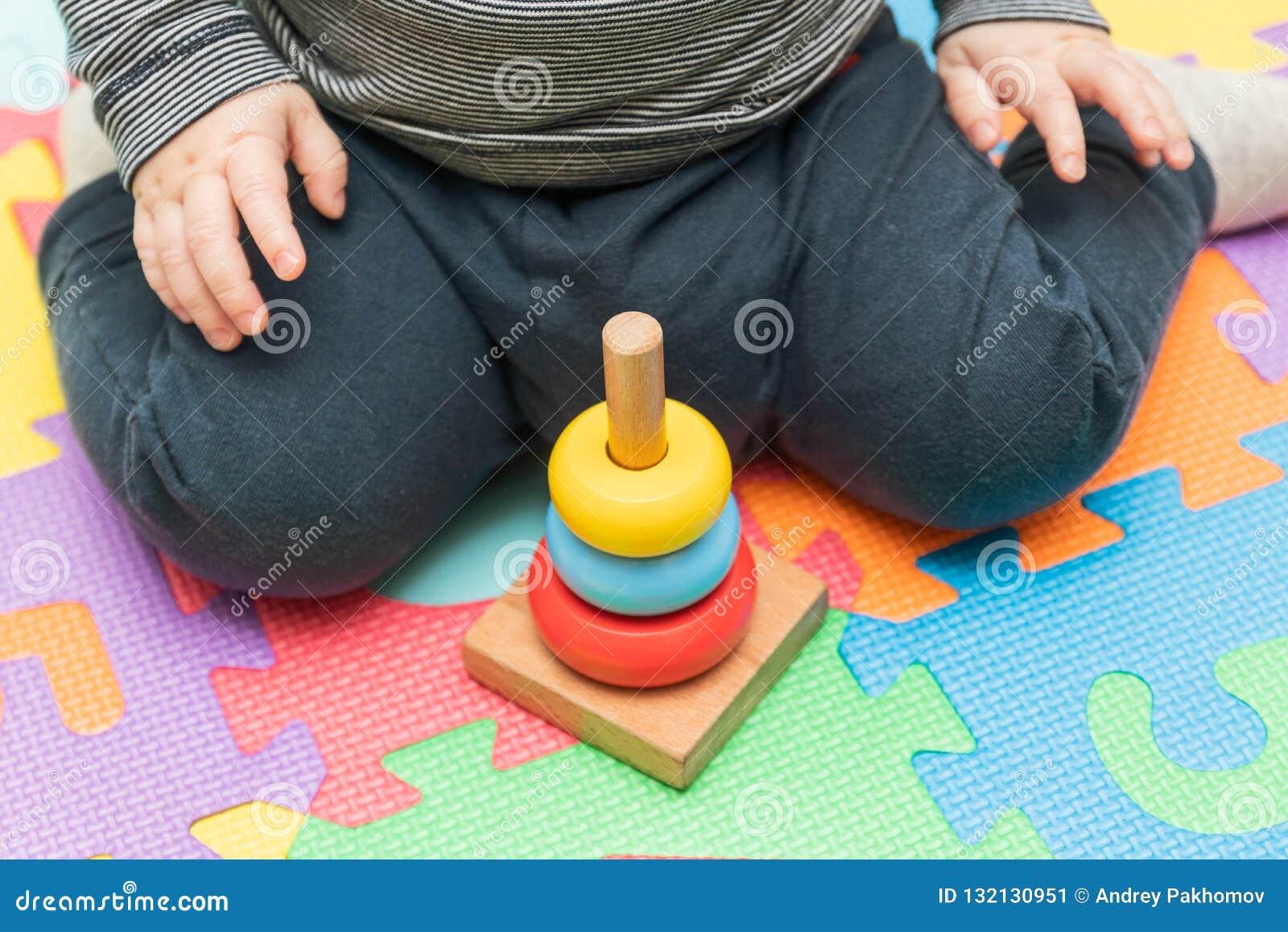 Um rapaz pequeno que senta-se em uma esteira de jogo, recolhe uma pirâmide das crianças multi-coloridas brinquedos educacionais p