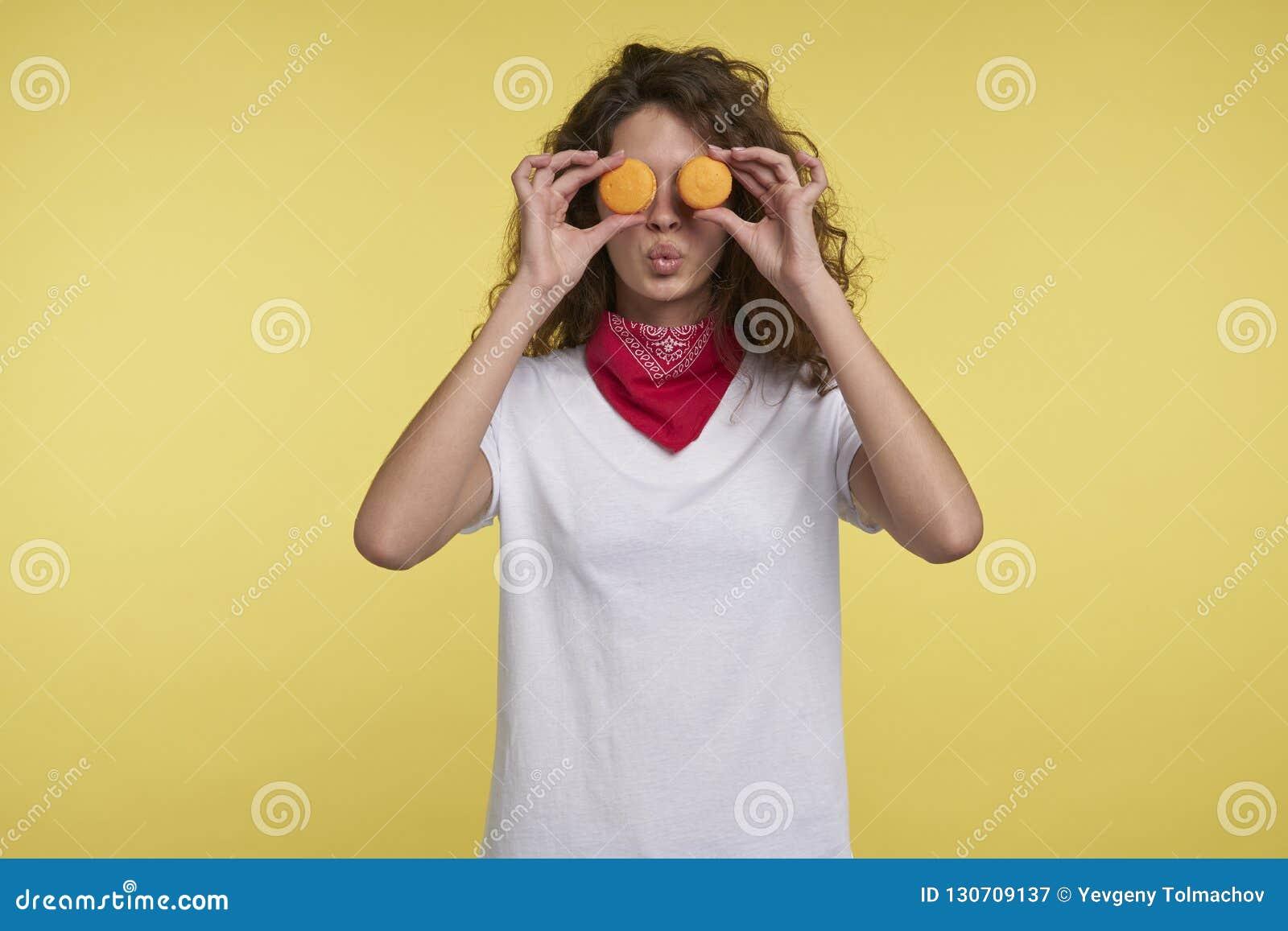 Um retrato da mulher italiana consideravelmente moreno e dos macarons sobre o fundo amarelo