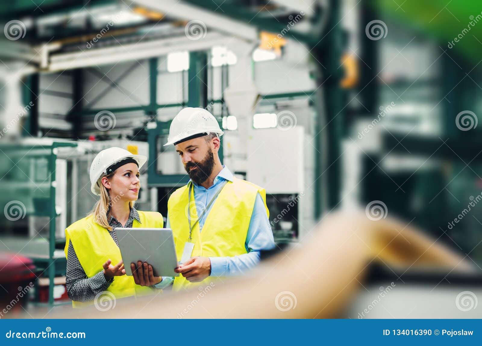 Um retrato de um coordenador industrial do homem e da mulher com tabuleta em uma fábrica