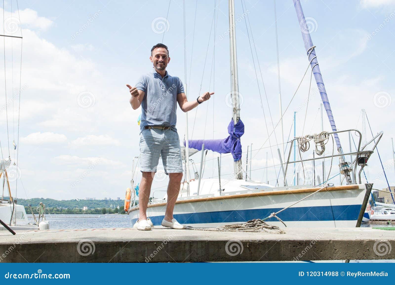 Um retrato de sorriso do  yachtsman  no cais com ambos os polegares acima rio e iate no fundo Marinheiro bem sucedido novo do hom