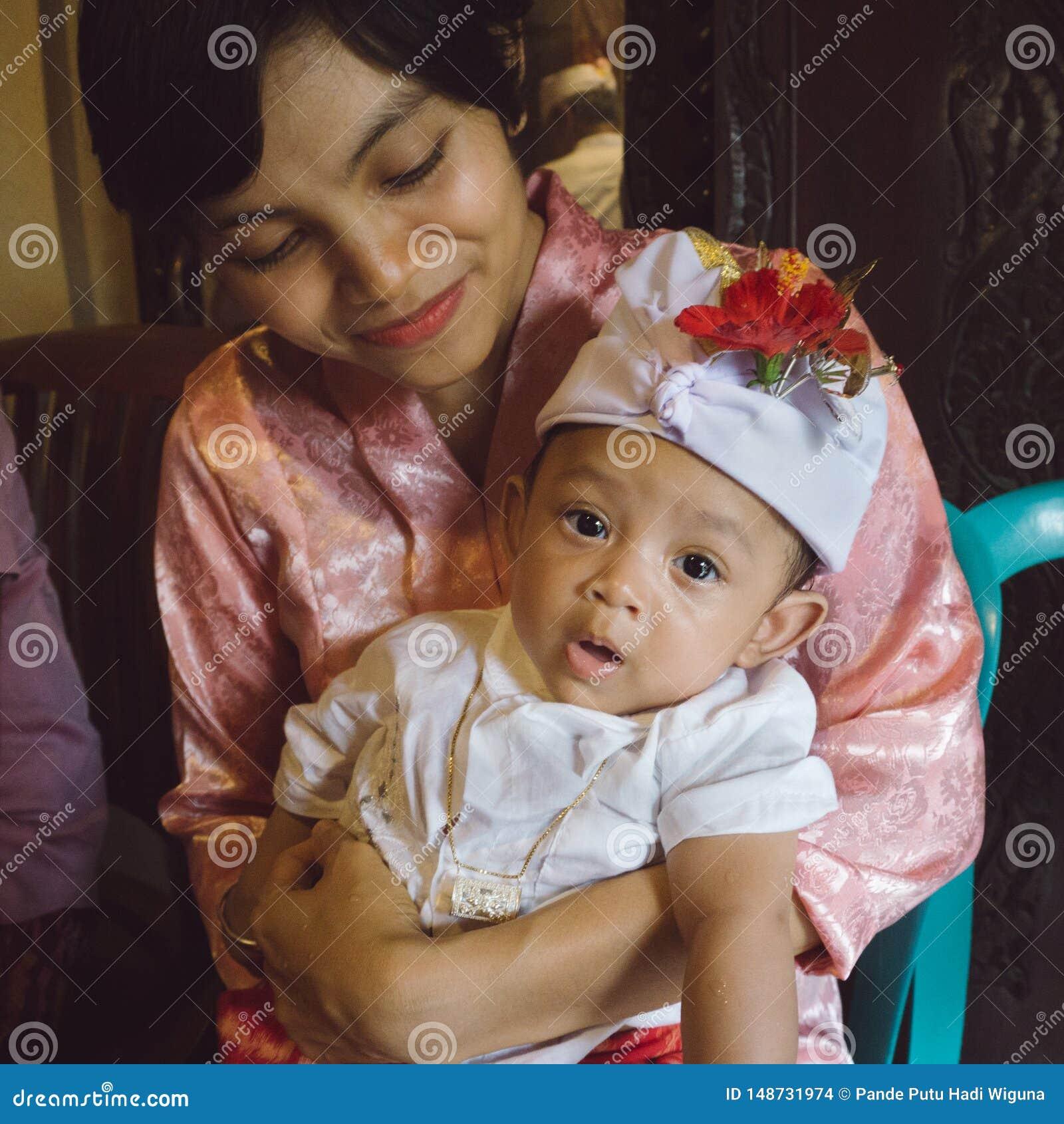Um retrato de uma mãe com seu bebê que tem 3 meses velho nos braços da mãe Os bebês levantam usando faixas e vermelho do Balinese
