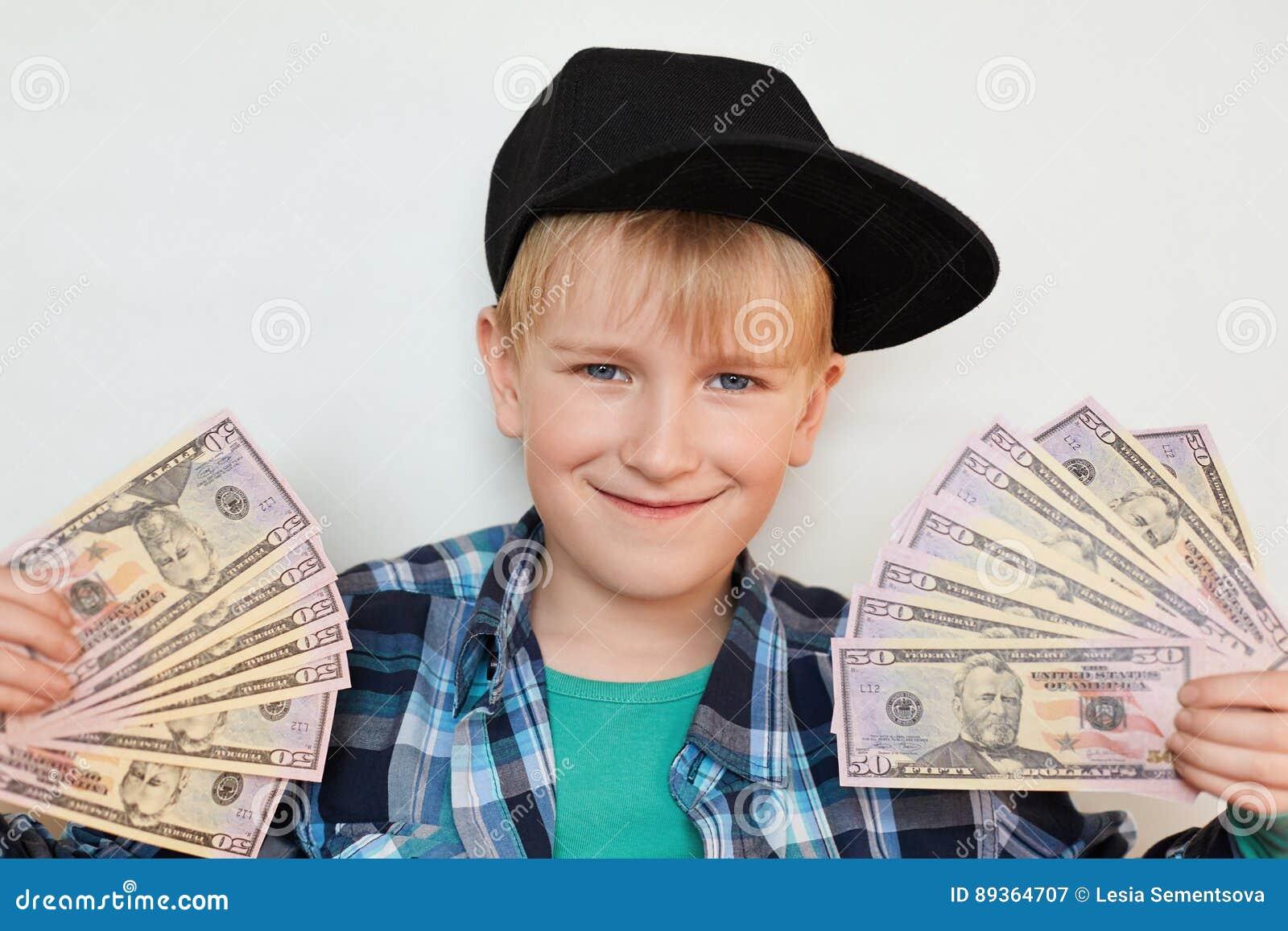 Um retrato do menino à moda pequeno deleitado no tampão preto que guarda o dinheiro em suas mãos Um homem feliz da criança que ma