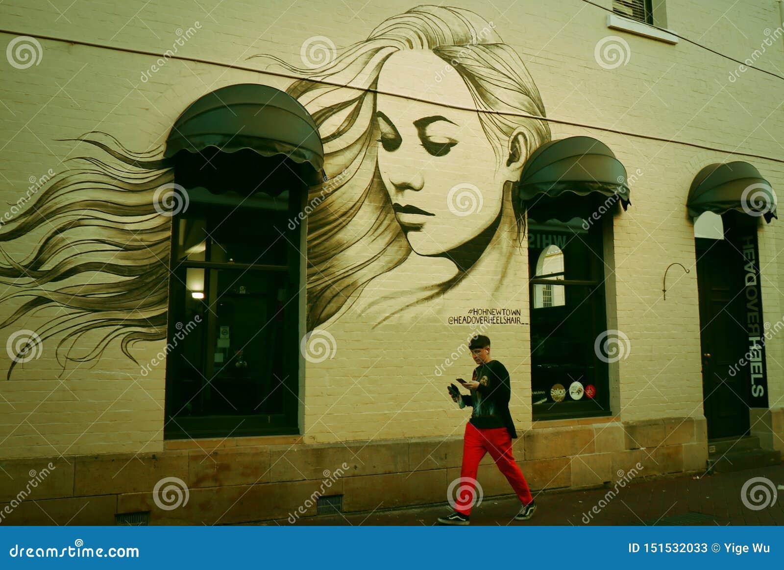 Um retrato graffitied da casa- de uma mulher bonita na parede