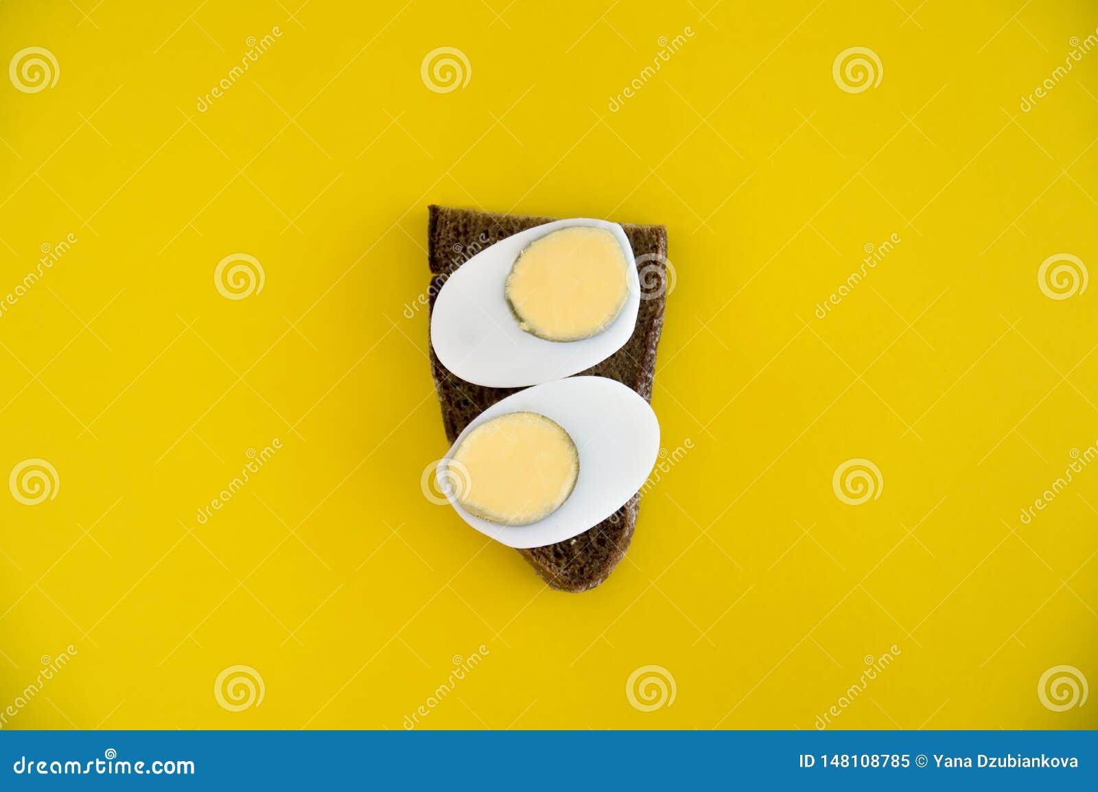 Um sanduíche de mentiras do pão e do ovo cozido de centeio em um fundo amarelo Café da manhã para a dieta Brinde com o café da ma