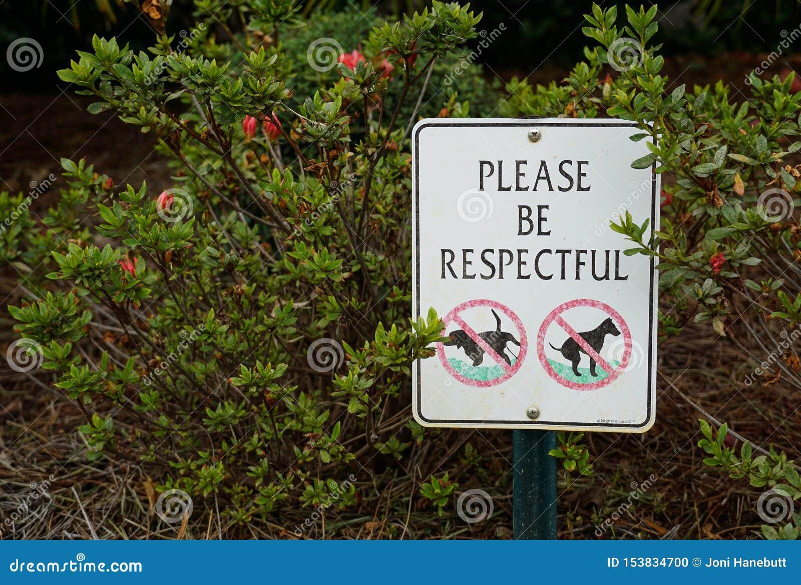 Um sinal com os arbustos no fundo