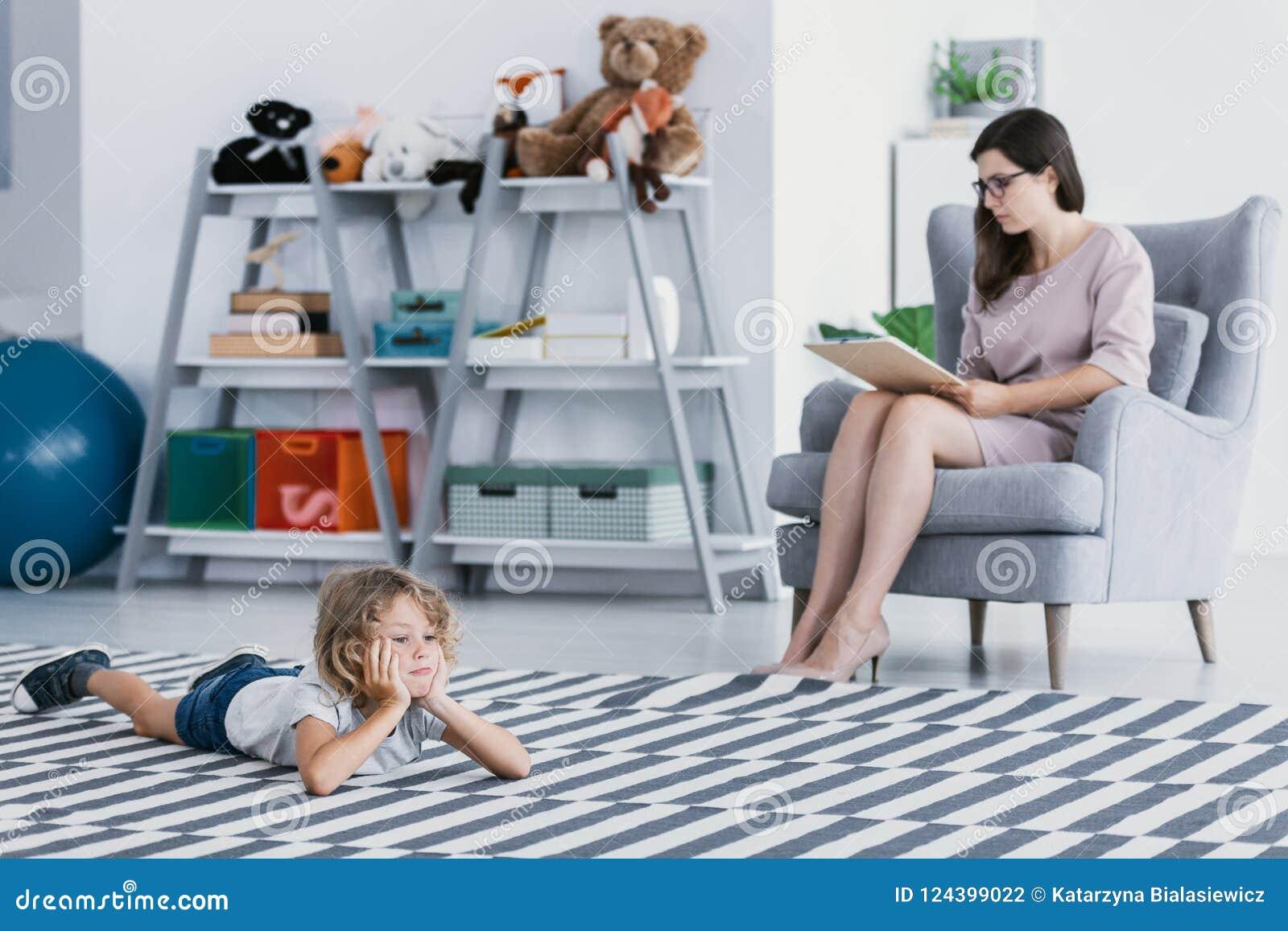 Um terapeuta profissional que faz um diagnóstico de uma criança retraída que se esteja encontrando no assoalho em um escritório d
