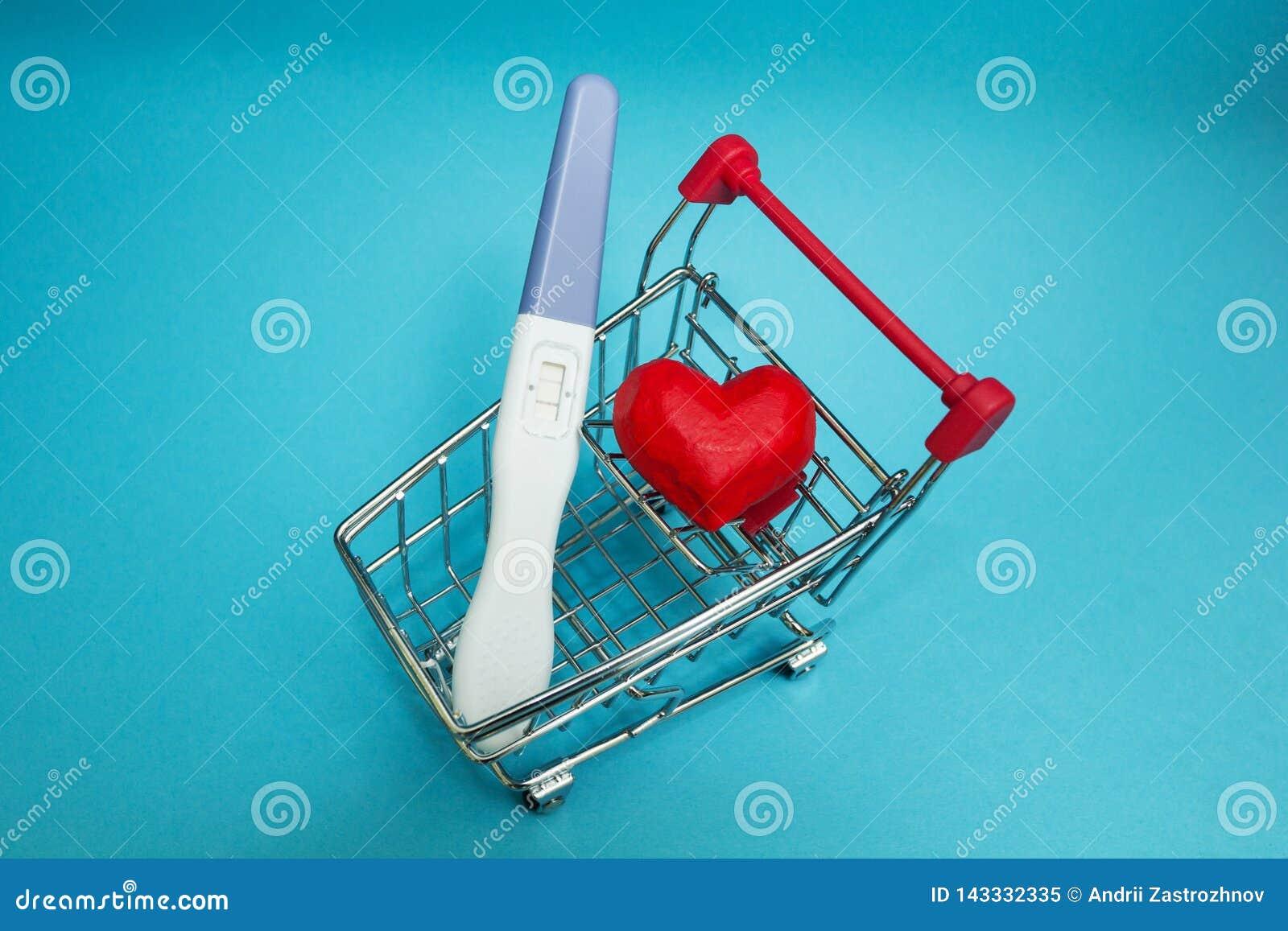 Um teste de gravidez positivo e um coração vermelho em um carrinho de compras