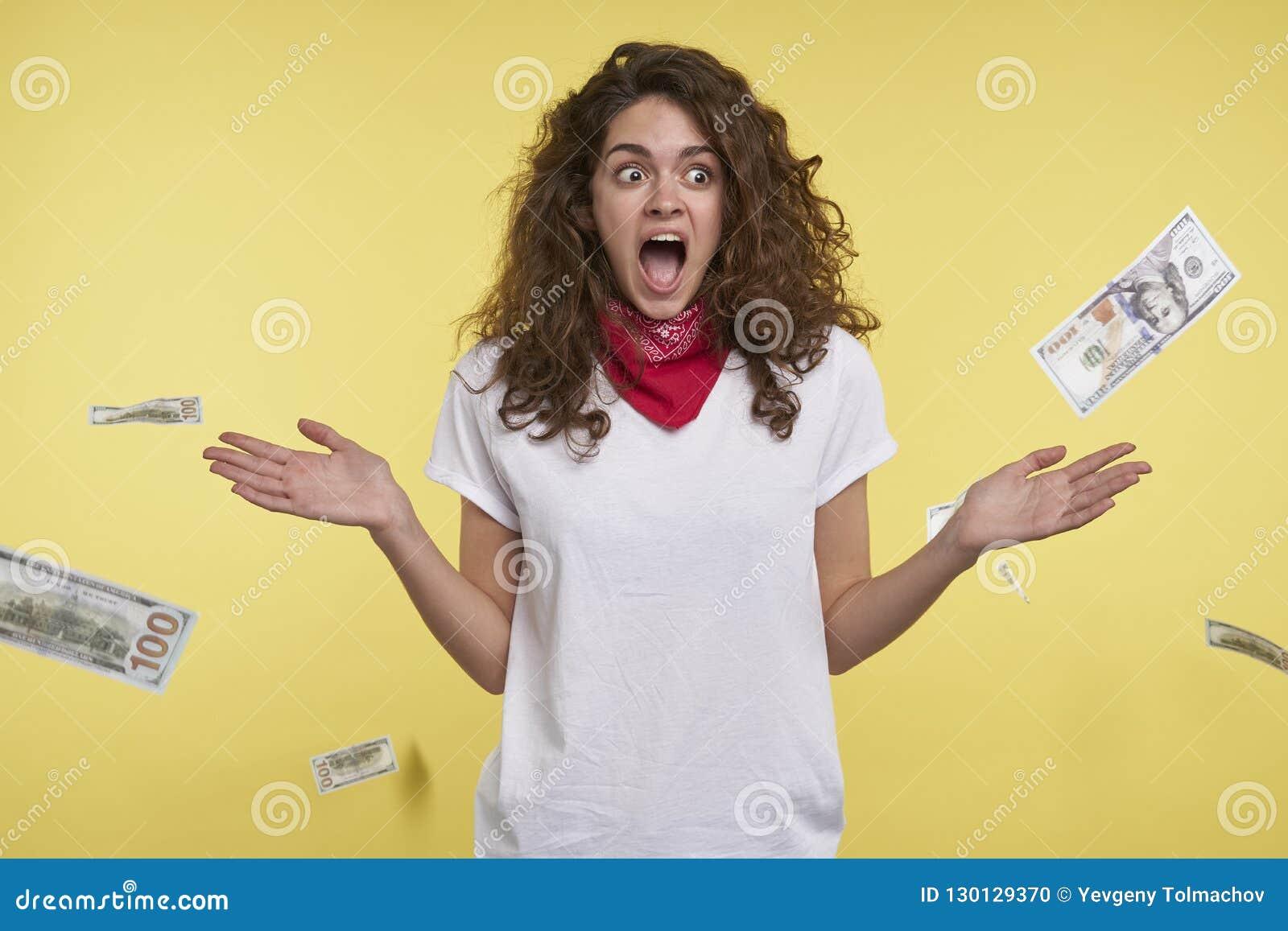 Um tiro do estúdio da mulher que ganha muito dinheiro, dinheiro que cai em sua cabeça, isolada sobre o fundo amarelo