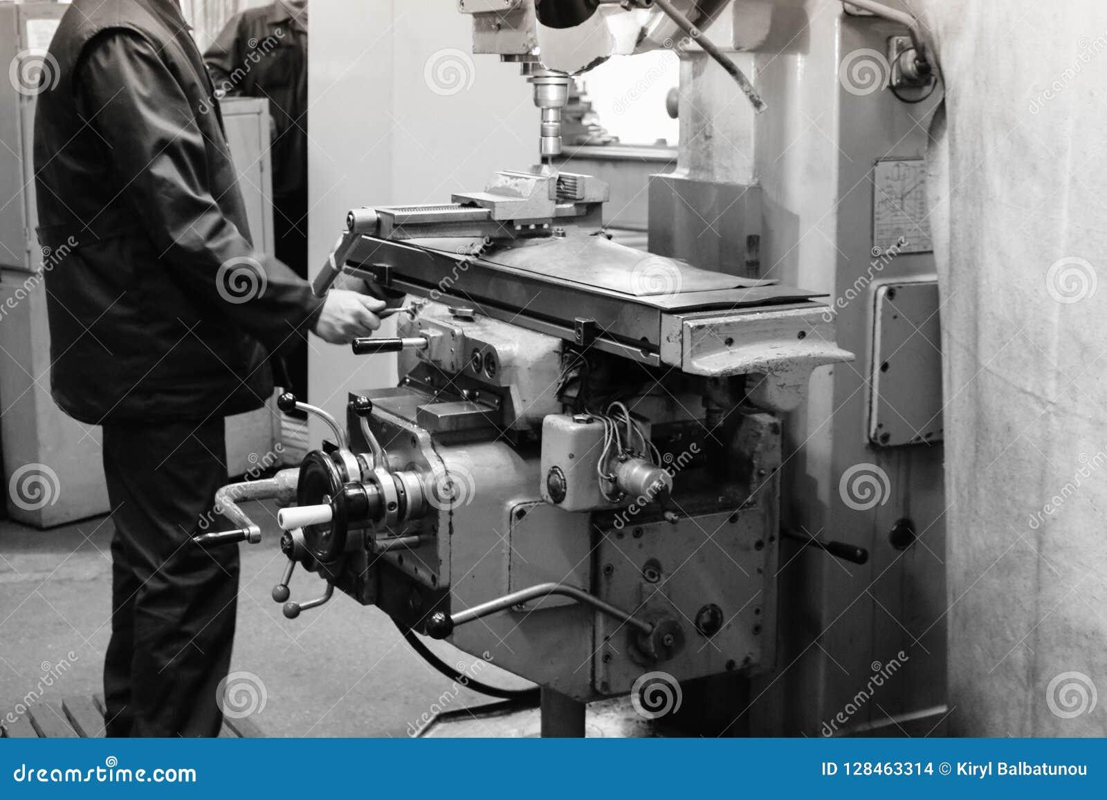 Um trabalhador masculino trabalha em um torno maior do serralheiro do ferro do metal, equipamento para reparos, trabalho do metal