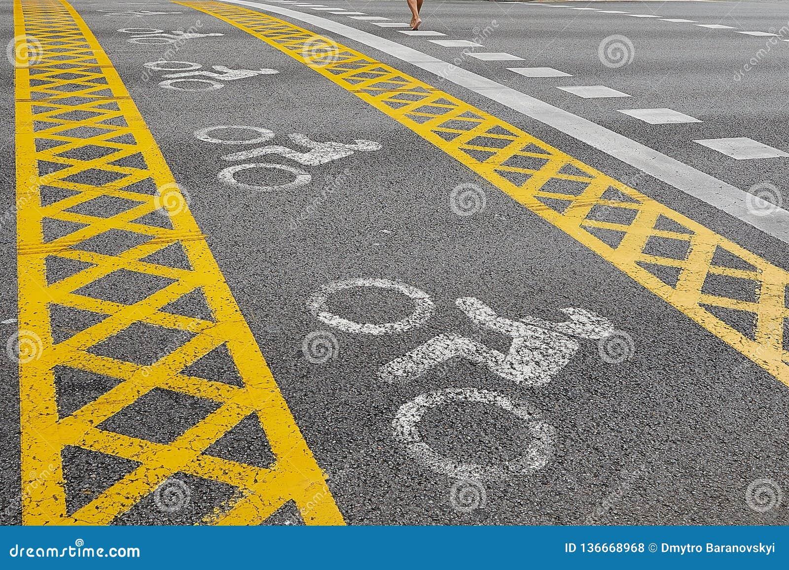 Um trajeto amarelo da bicicleta cruza a estrada O homem vai