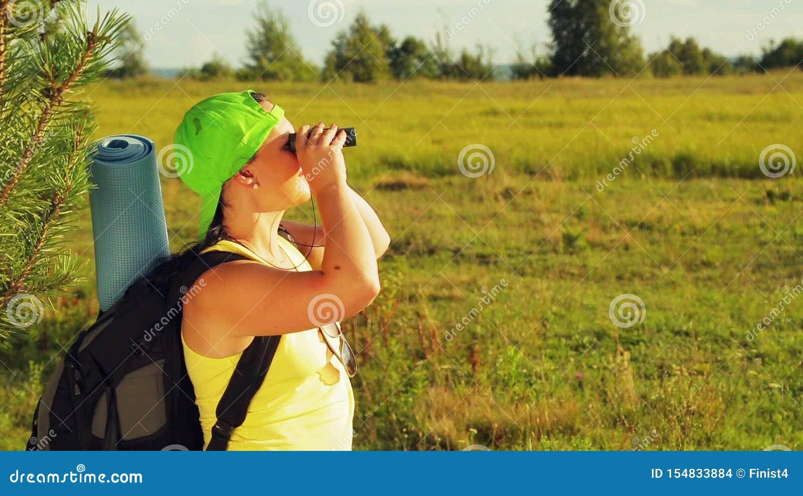 Um turista da mulher está em uma clareira e em olhares da floresta através dos binóculos aonde ir em seguida vídeos de arquivo