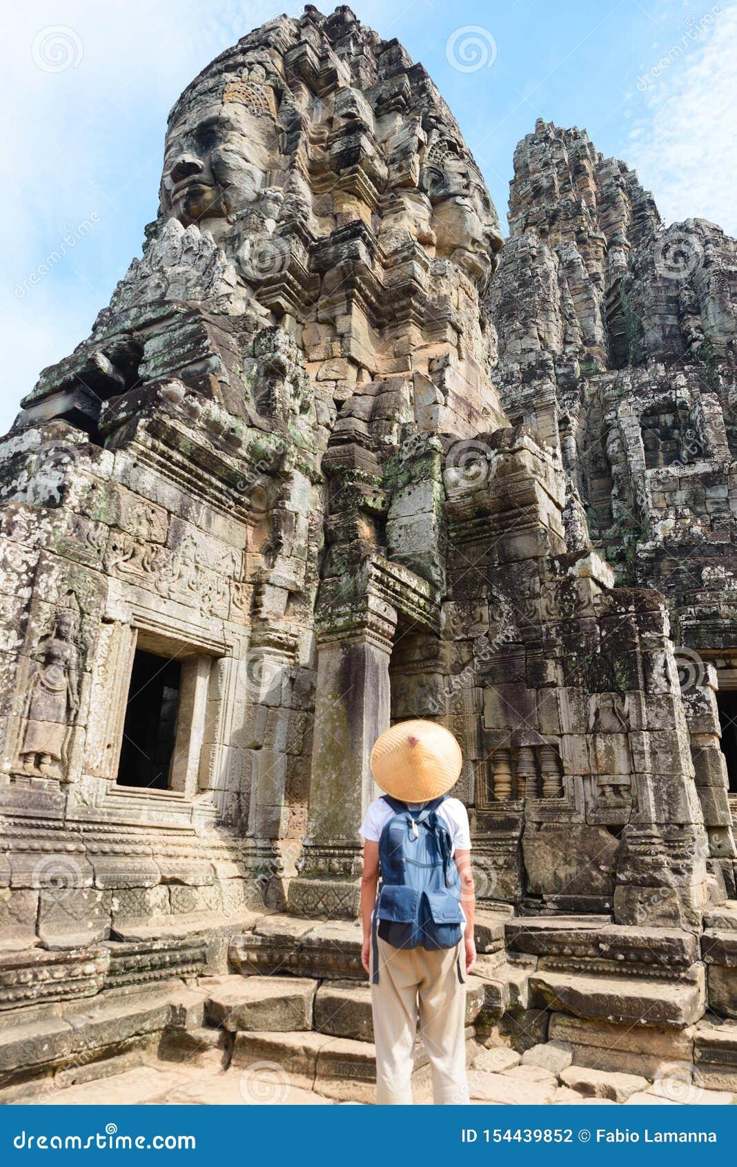 Um turista que visita ruínas de Angkor entre a selva, complexo do templo de Angkor Wat, destino Camboja do curso Mulher com chap