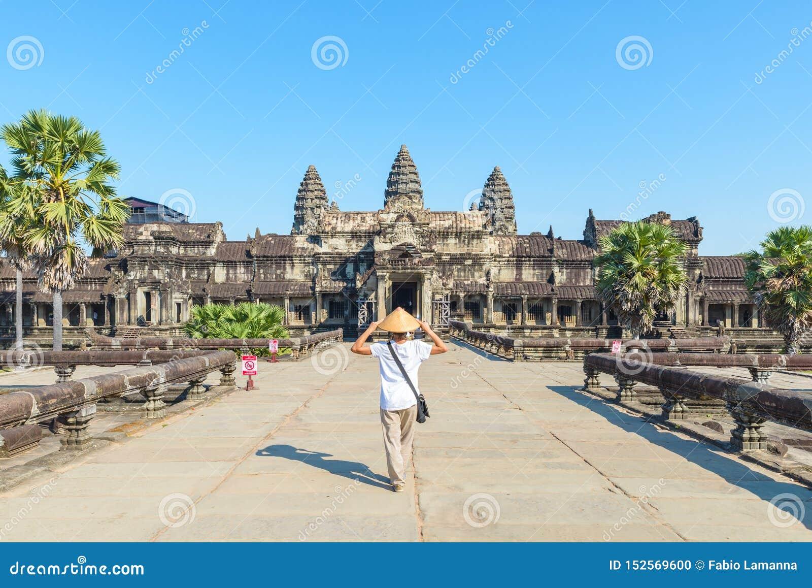 Um turista que visita ru?nas de Angkor Wat no nascer do sol, destino Camboja do curso Mulher com chap?u tradicional e os bra?os a