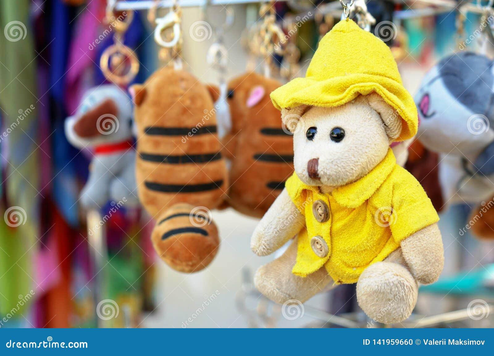 Um urso de peluche pequeno em um revestimento amarelo e em um chapéu