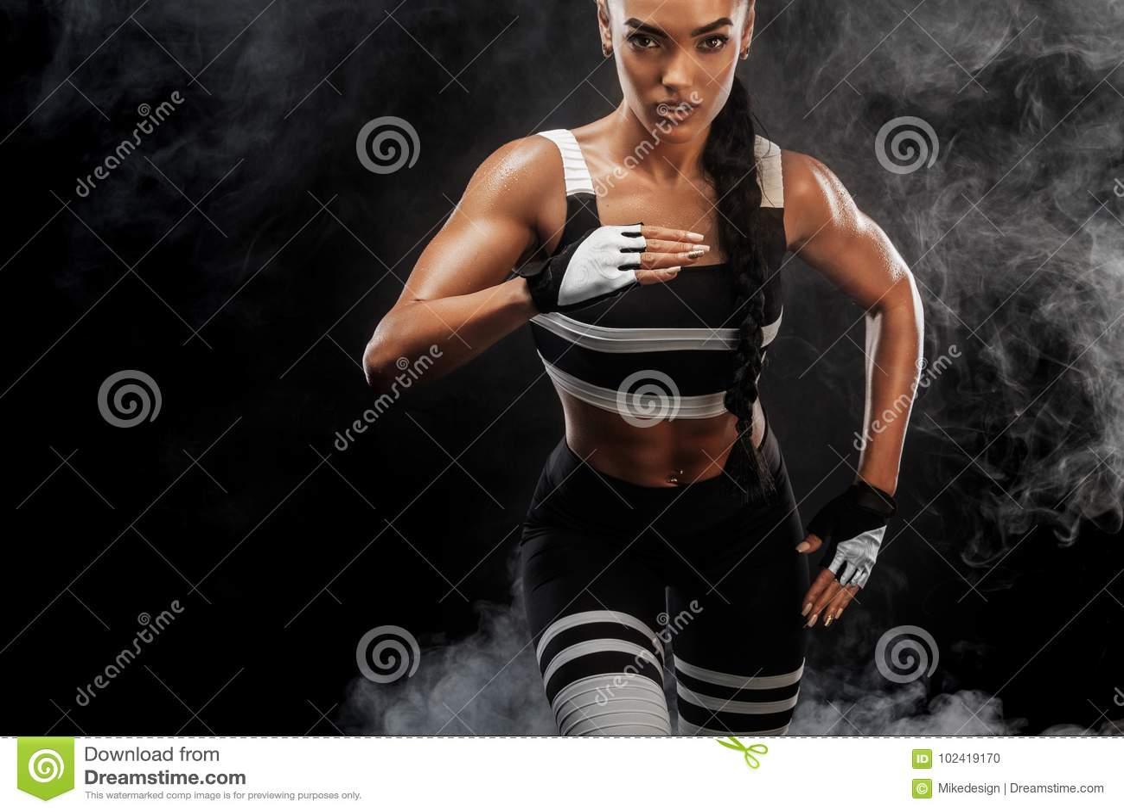 Um velocista atlético, fêmea forte, correndo no nascer do sol que veste no conceito da motivação do sportswear, da aptidão e do e