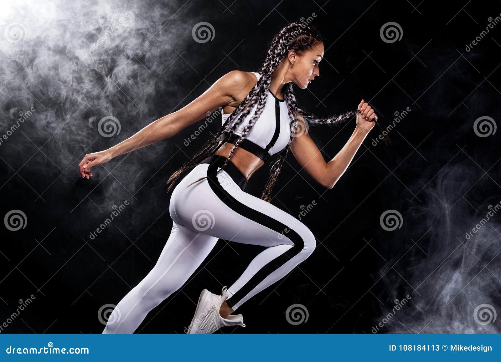 Um velocista forte atlético, da mulher, correndo no fundo preto que veste na motivação do sportswear, da aptidão e do esporte