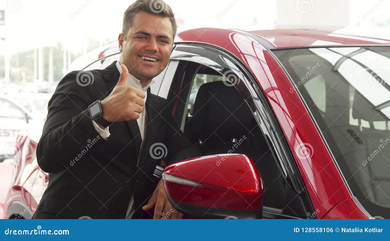 Um vendedor alegre aponta à qualidade excelente do carro