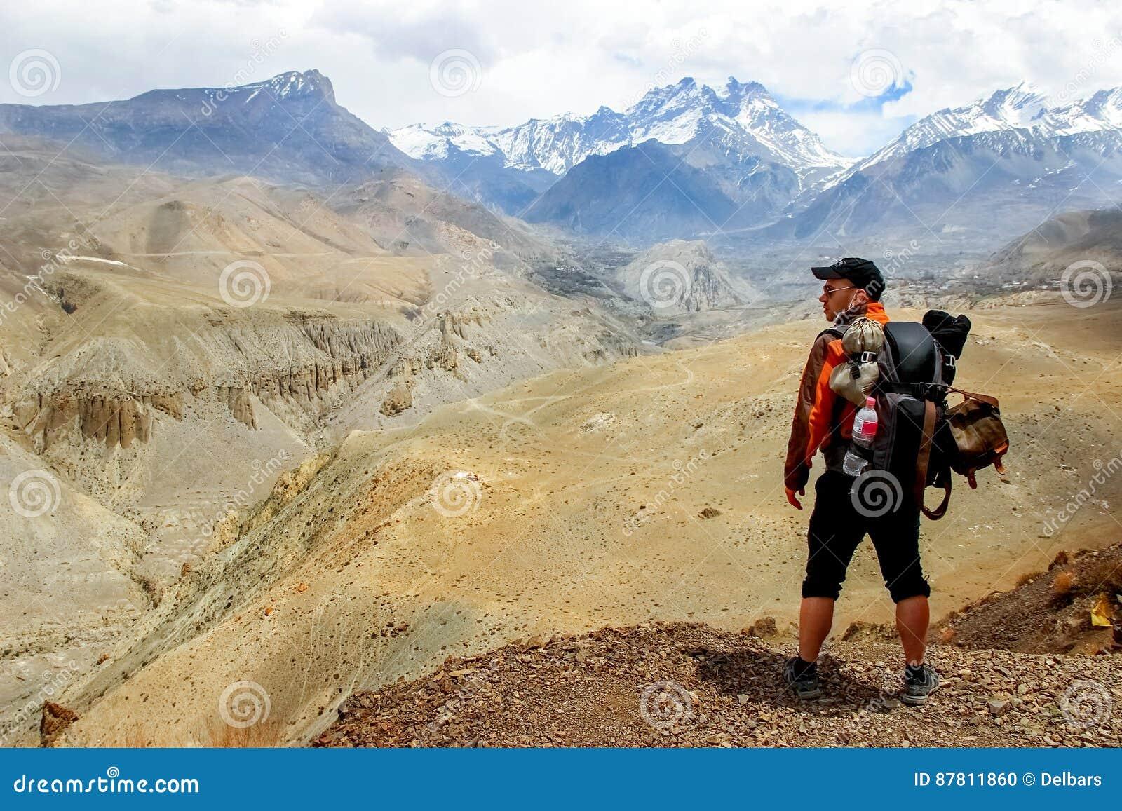Um viajante com uma trouxa nas montanhas Himalaias olha o desfiladeiro nepal Reino do mustang superior