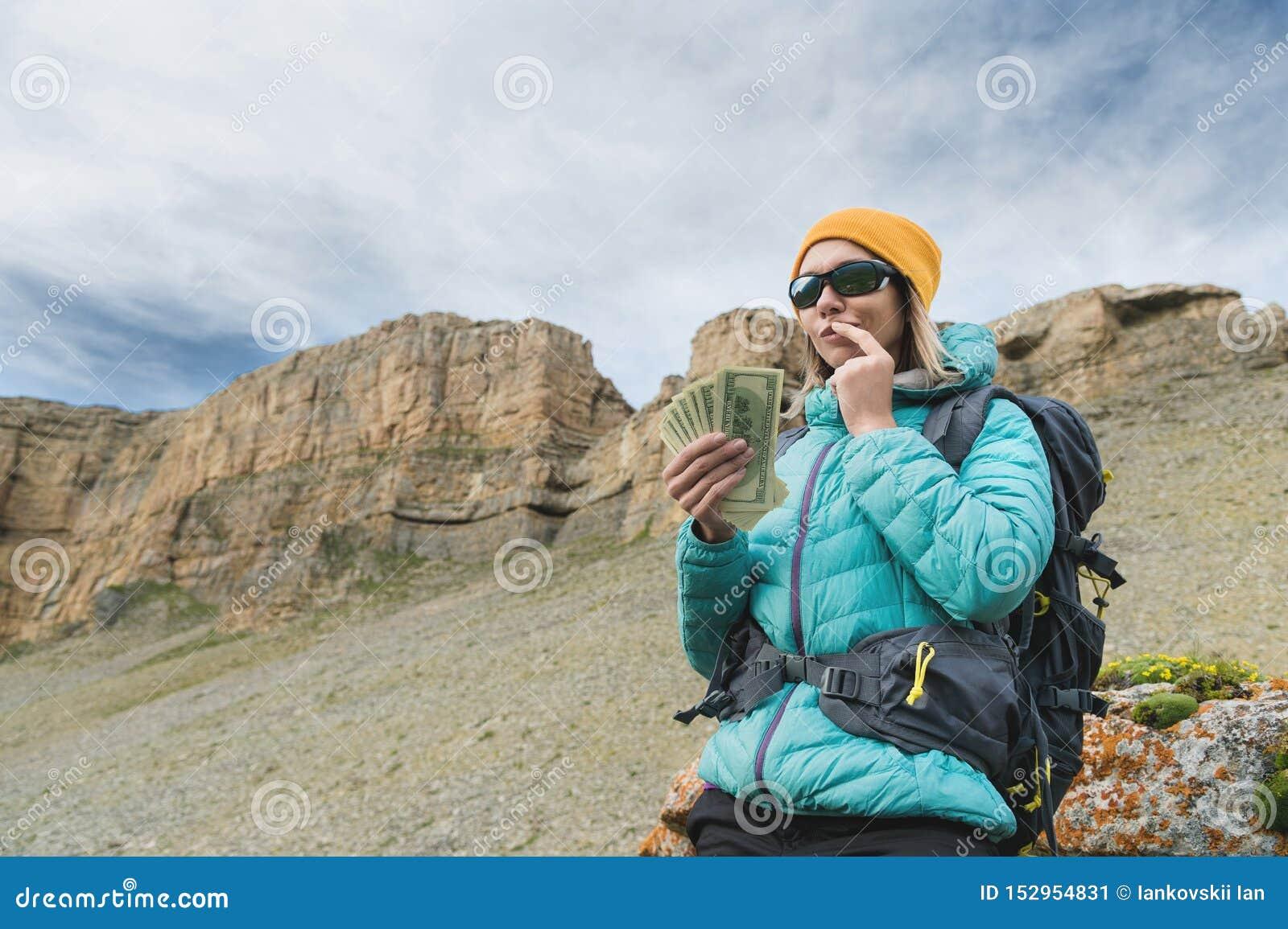 Um viajante da menina nos óculos de sol e com uma trouxa no fundo de rochas da montanha alta guarda pensativamente um
