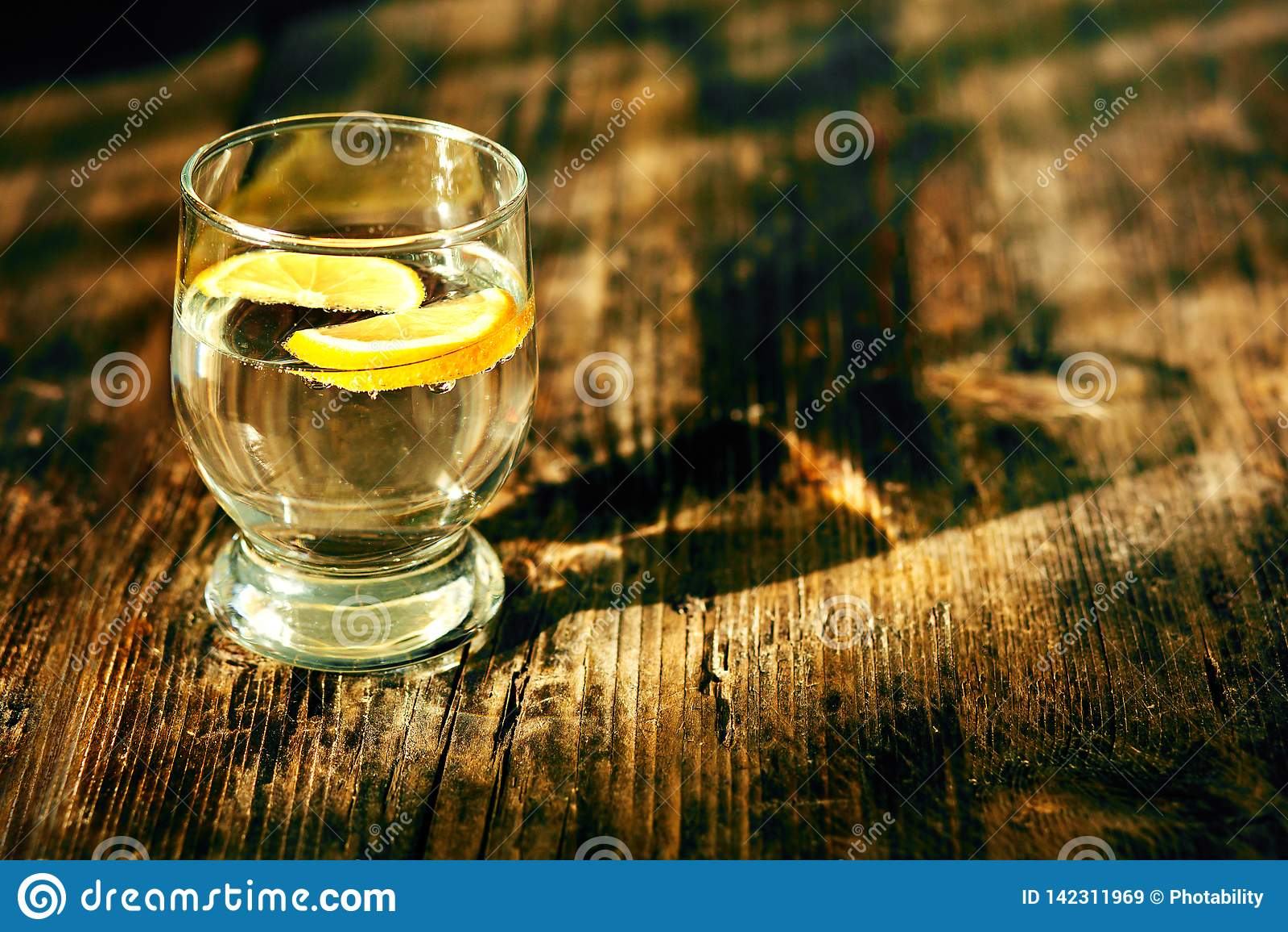 Um vidro da água e de um limão
