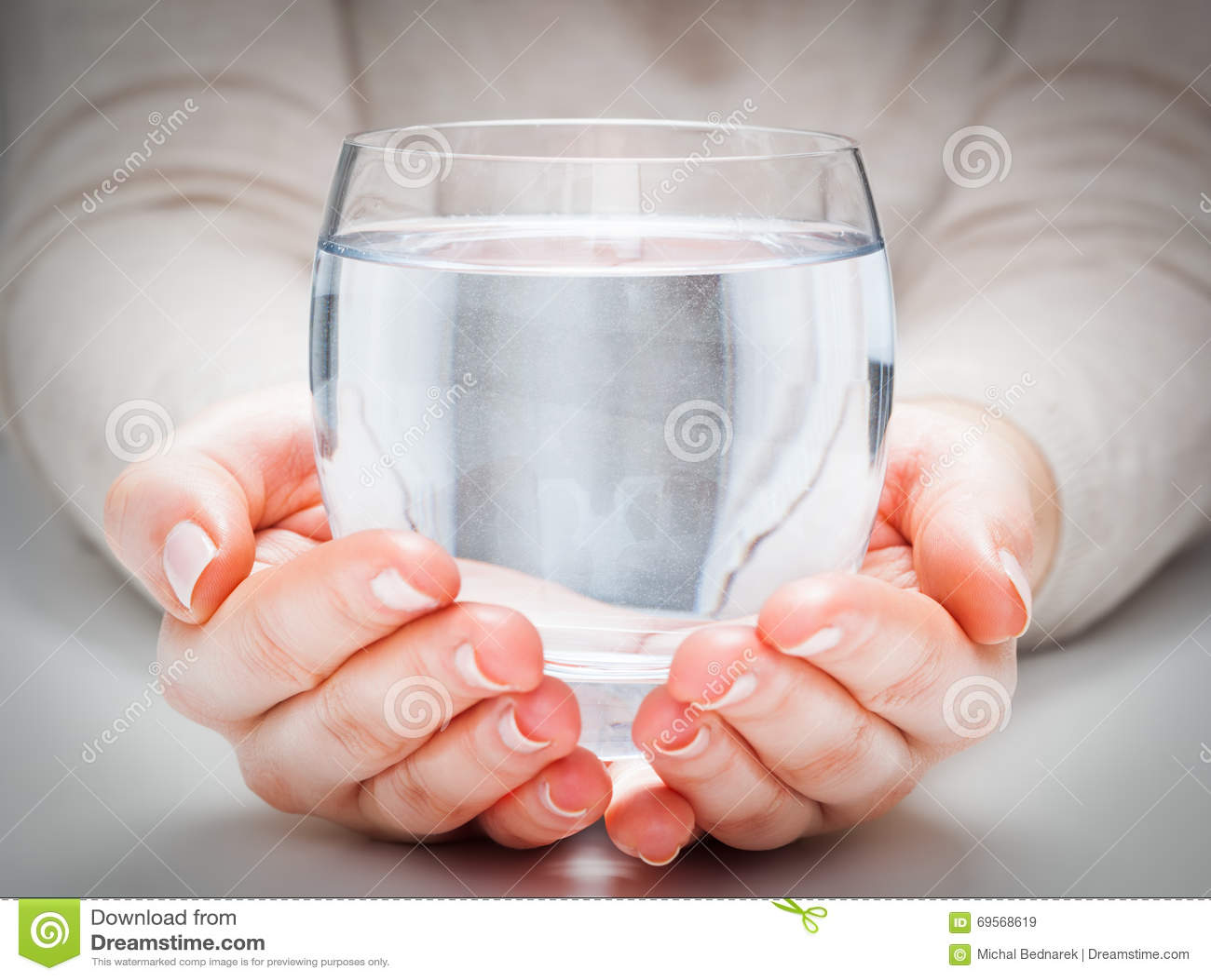 Um vidro da água mineral limpa nas mãos da mulher Proteção ambiental, bebida saudável