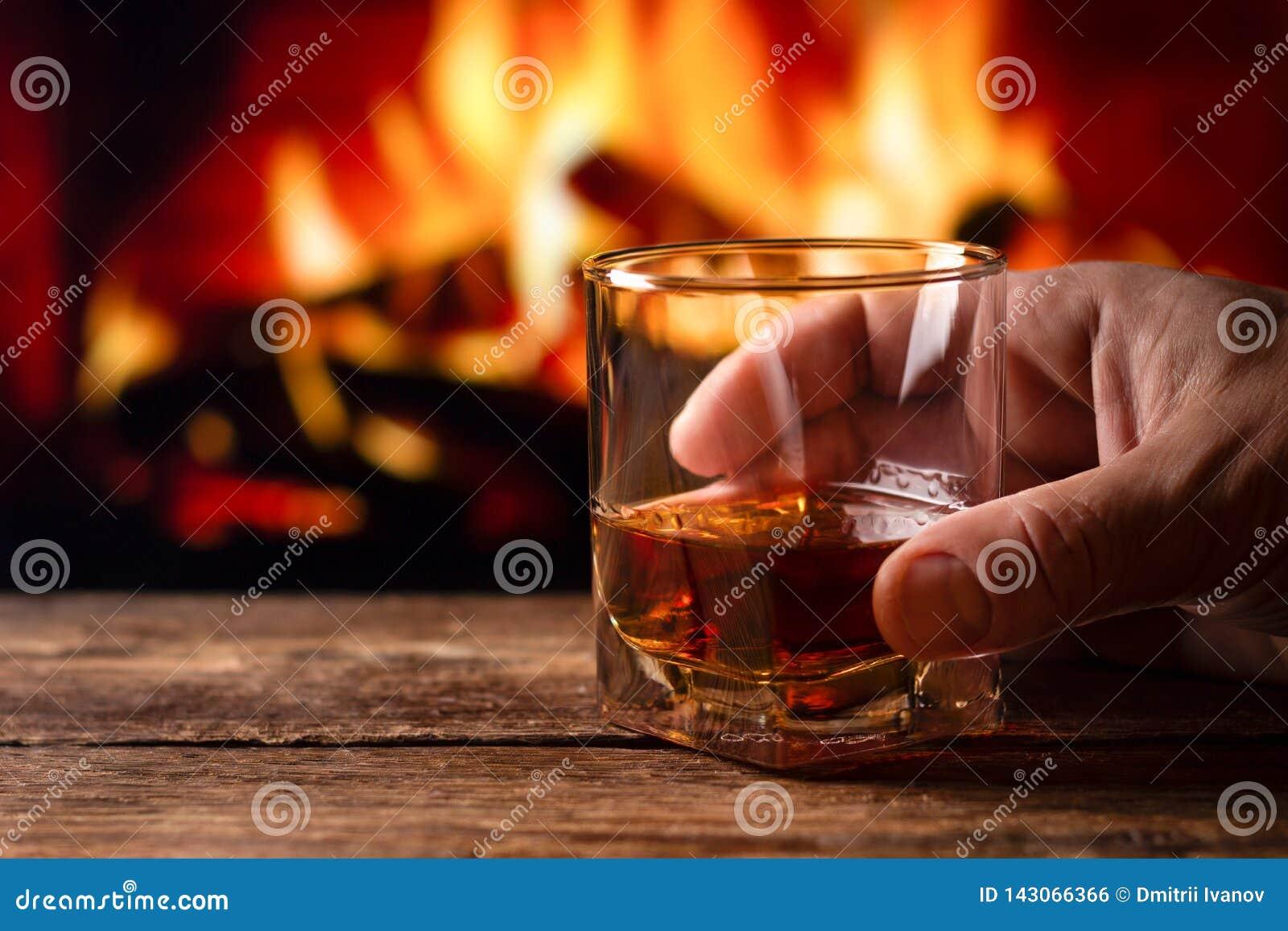 Um vidro do uísque em uma mão do homem