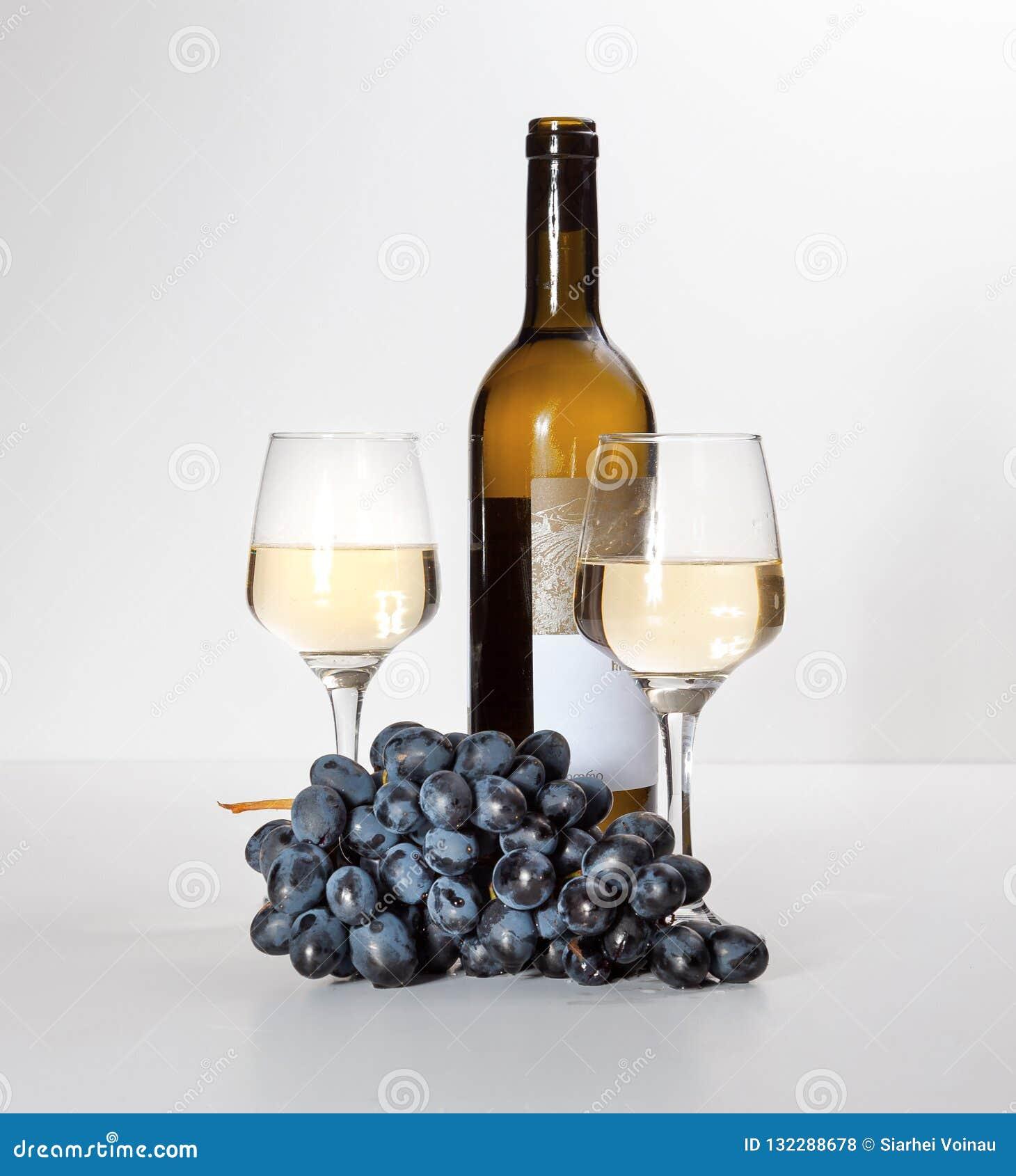 Um vidro do vinho branco, um grupo de uvas, uma garrafa aberta