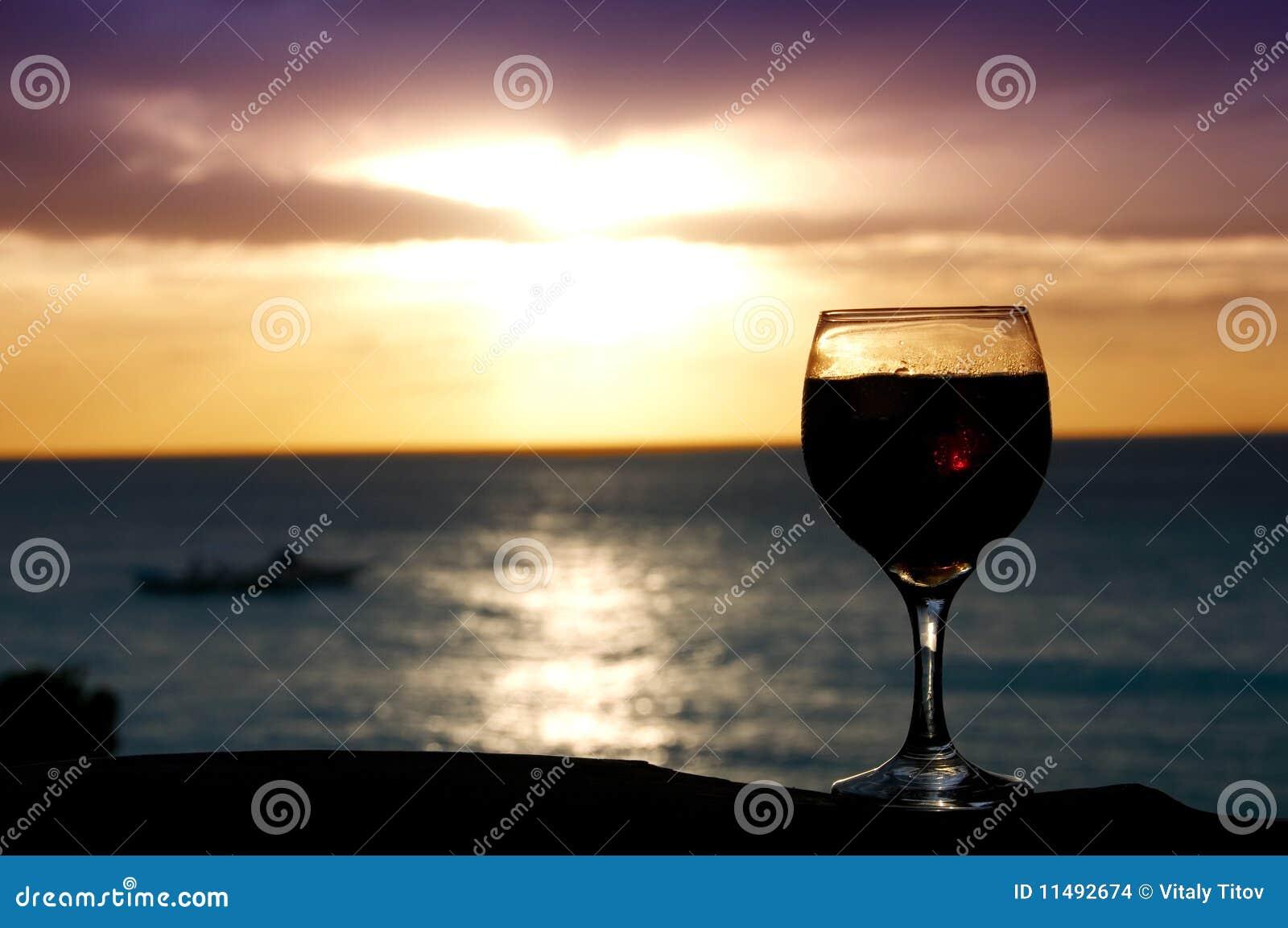 Um vidro do vinho no por do sol