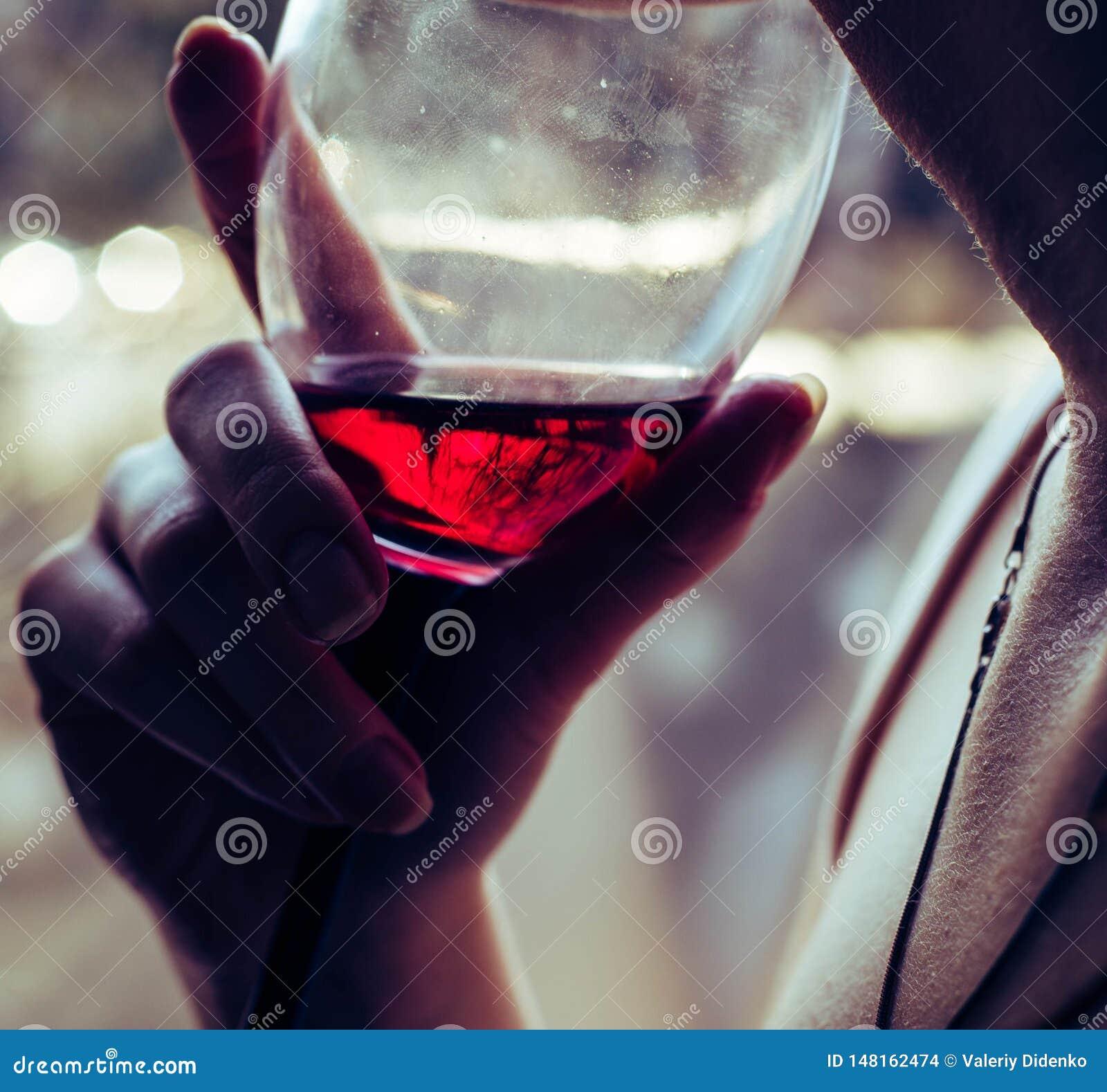 Um vidro do vinho tinto nas m?os de uma menina