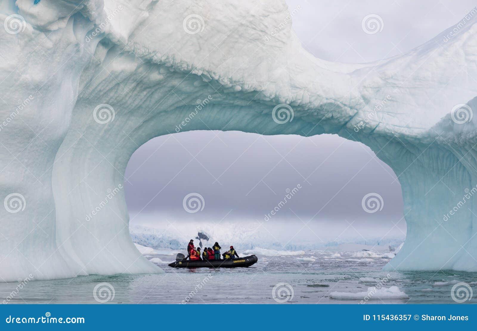 Um zodíaco completamente do turista visto através de um arco em um grande iceberg, a Antártica