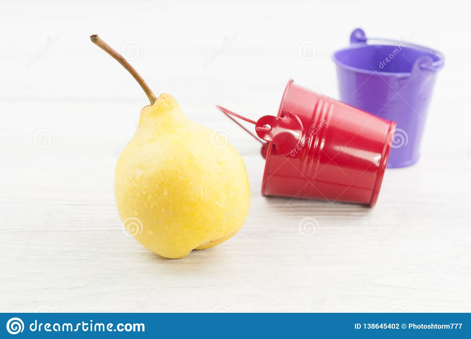 Uma única pera inteira madura amarela fresca e cubetas vermelhas e violetas vazias do metal