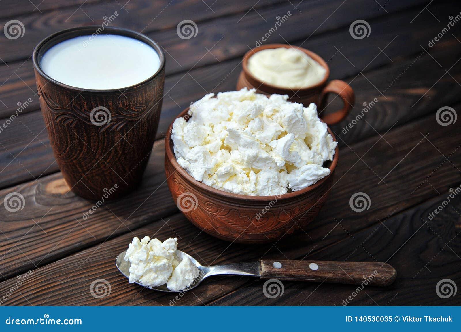 Uma bacia de argila com requeijão, uma caneca de argila com creme de leite, uma caneca com leite e uma colher em uma tabela