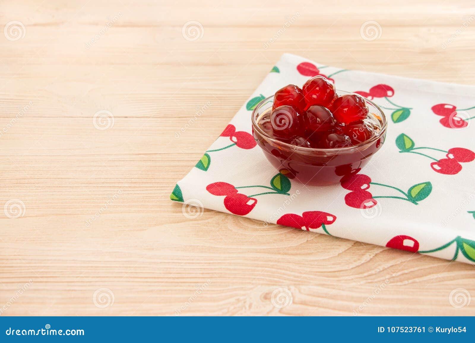 Uma bacia de cereja adoçada frutifica em um guardanapo com cerejas, espaço da cópia