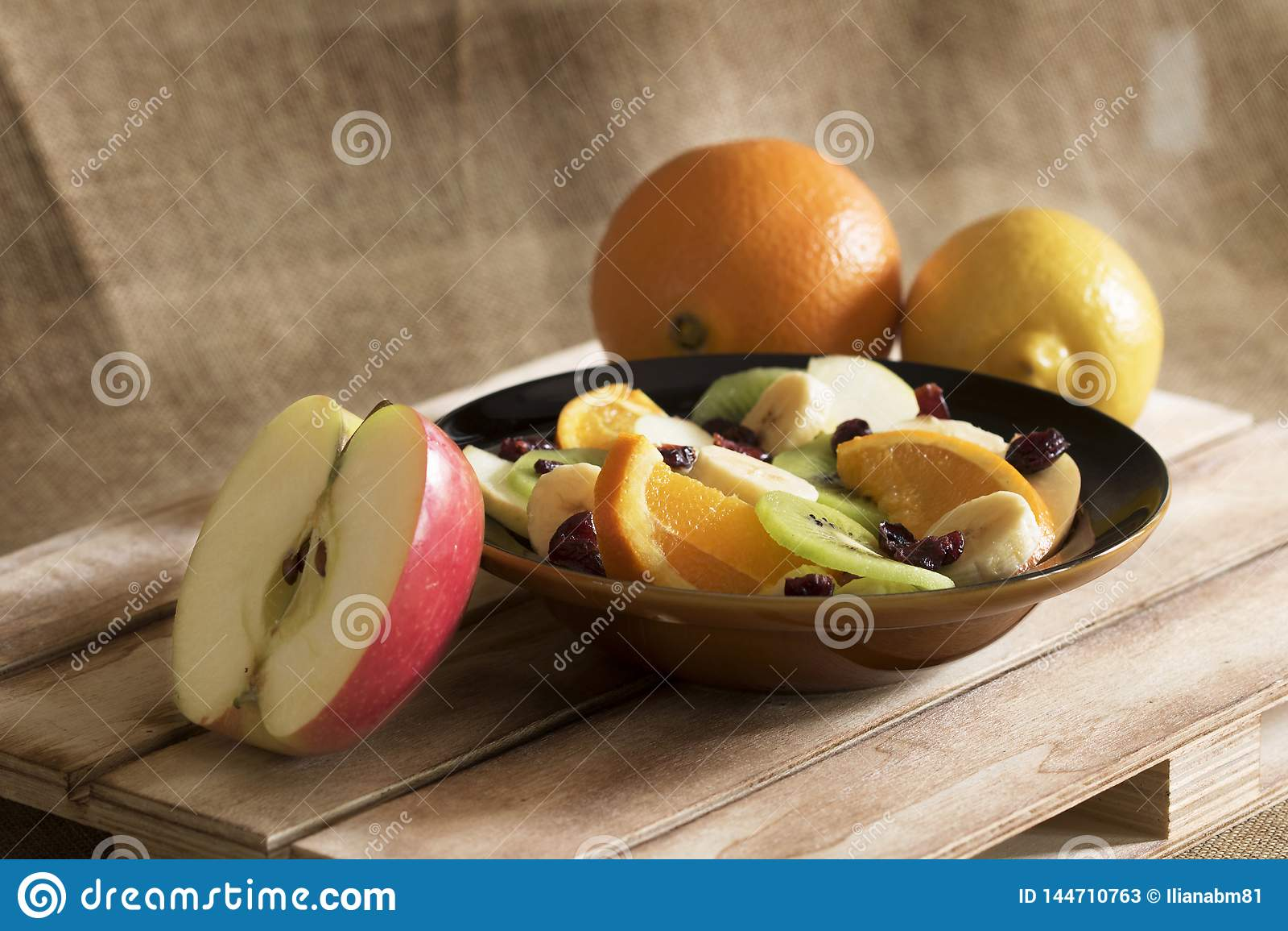 Uma bacia de salada de fruto, de uma laranja, de um limão e de maçã da metade