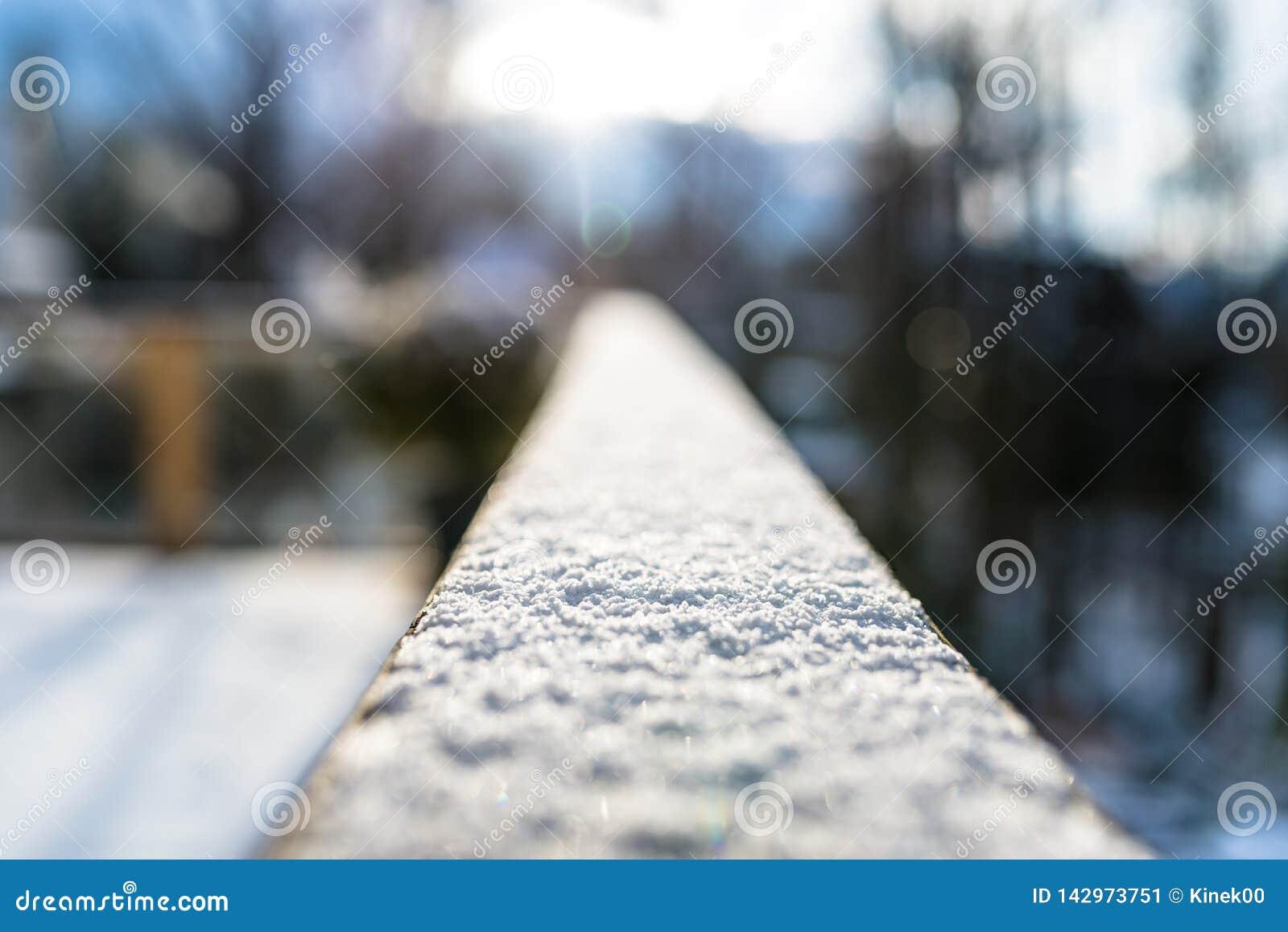 Uma balaustrada coberto de neve, de madeira no balc?o com foco seletivo No fundo, nas constru??es borradas e nas ?rvores