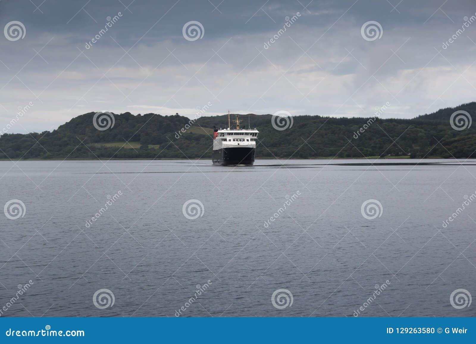 Uma balsa que aproxima um porto na costa de Escócia em um dia de verões frio